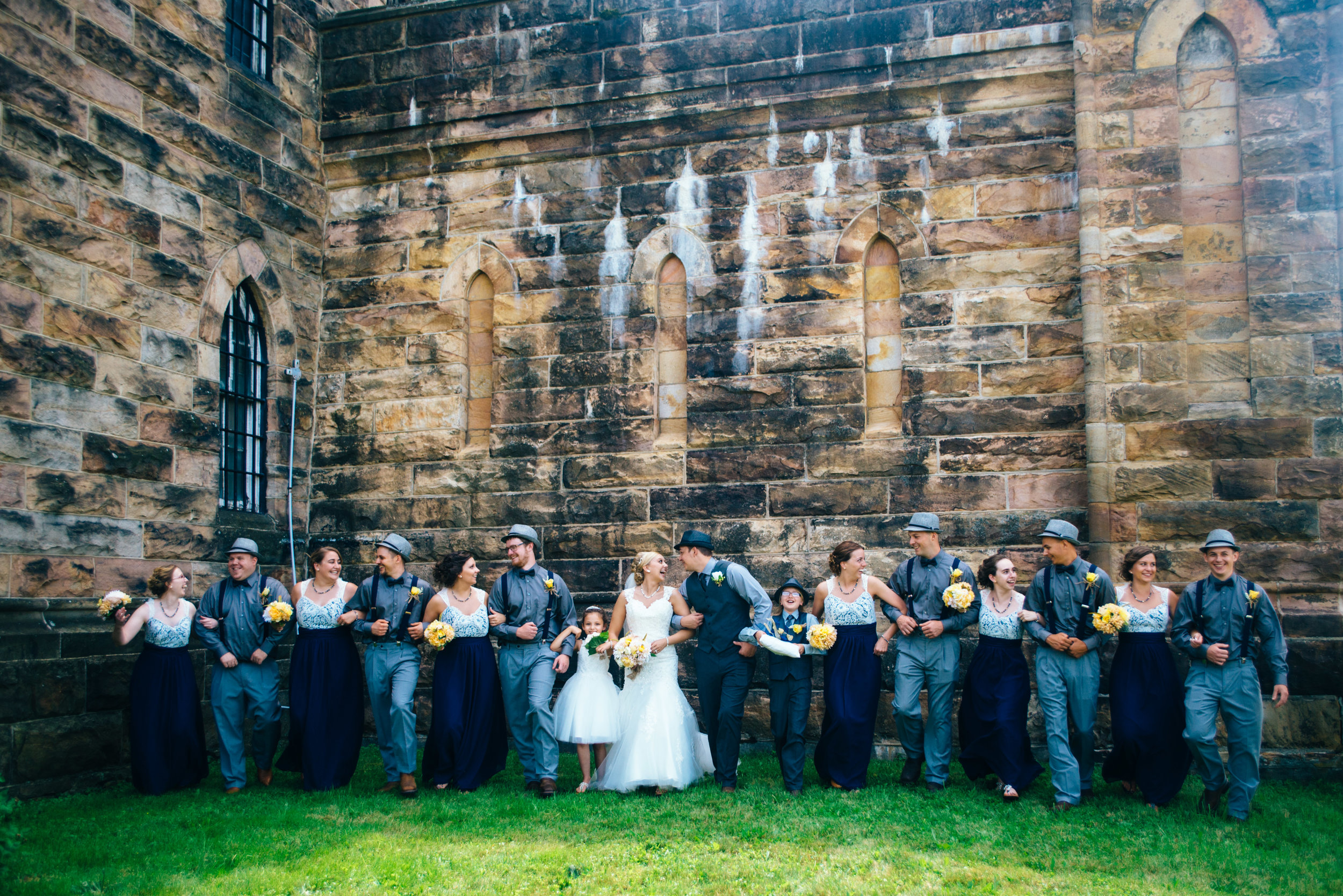 Bridal party walking and laughing in front of old Cambria County Jail in Ebensburg, PA