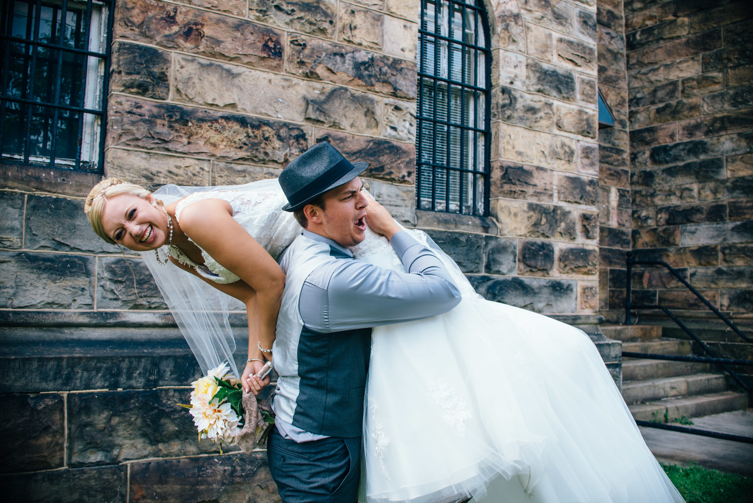 Groom throwing bride over shoulder and smacking buttFedora and Suspenders Wedding