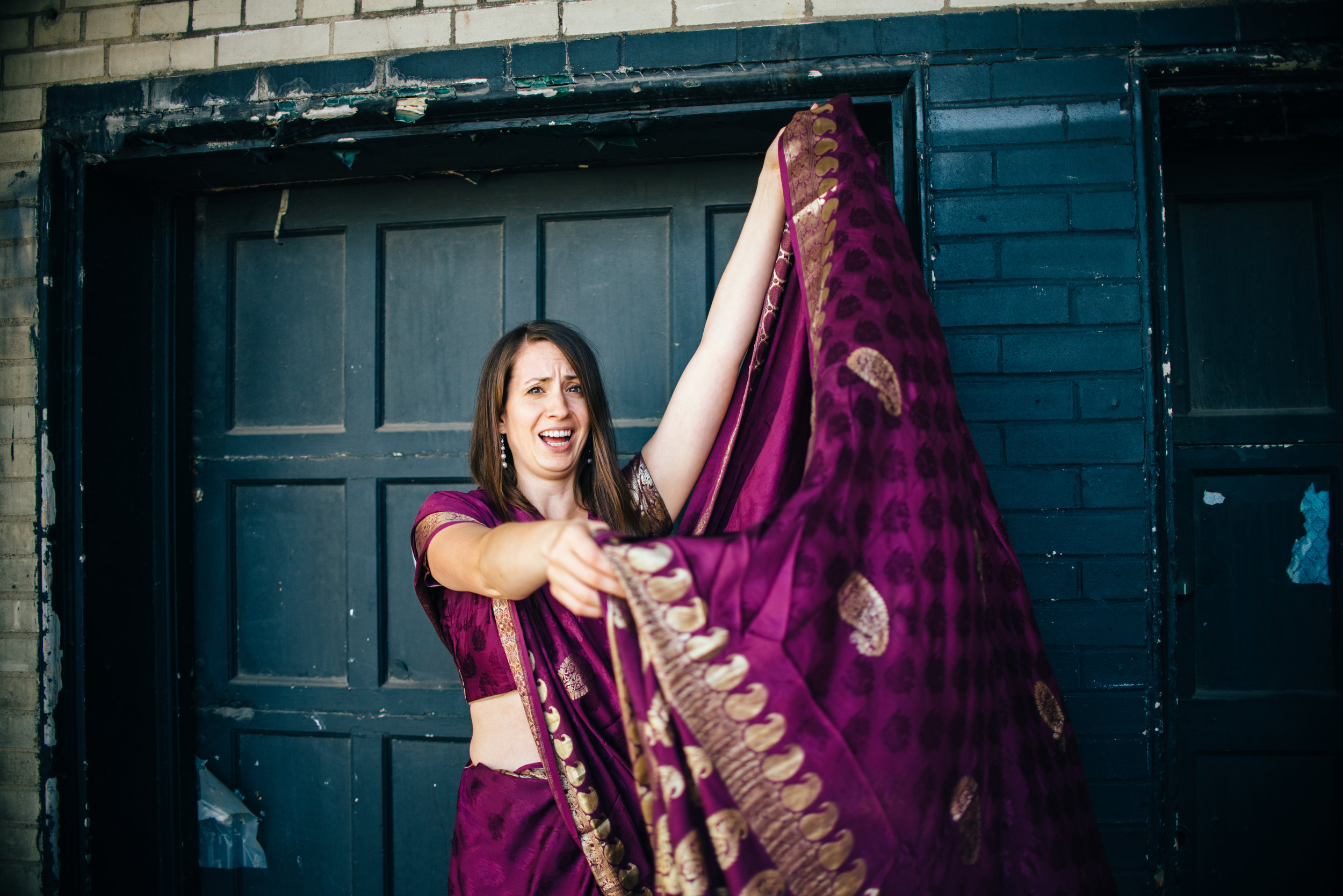 dark haired model wearing a purple and gold sari for a bridesmaid dress looking confused on how to tie a sari