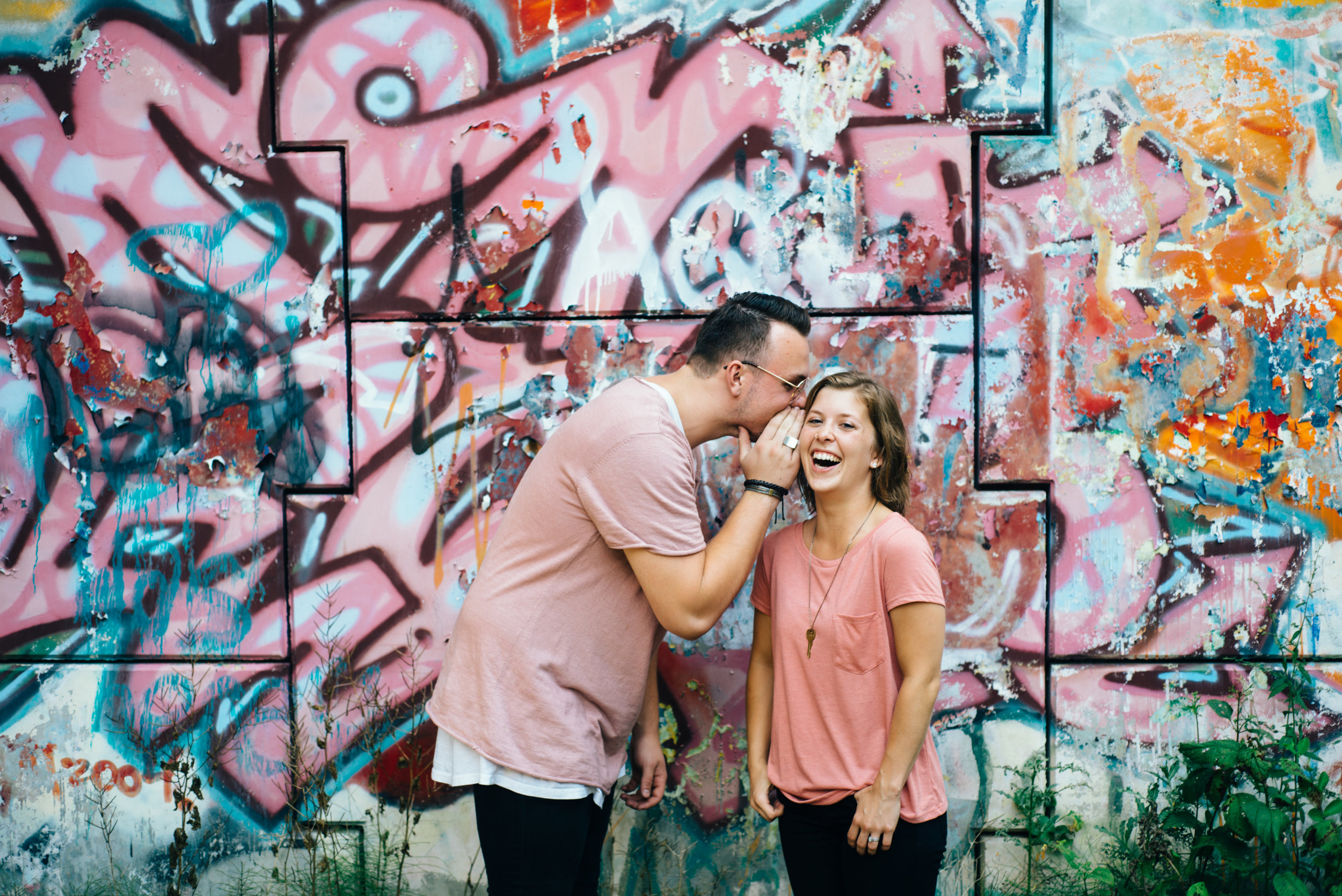 Young hip couple wearing pink shirts and black skinny jeans in front of pink graffiti wall