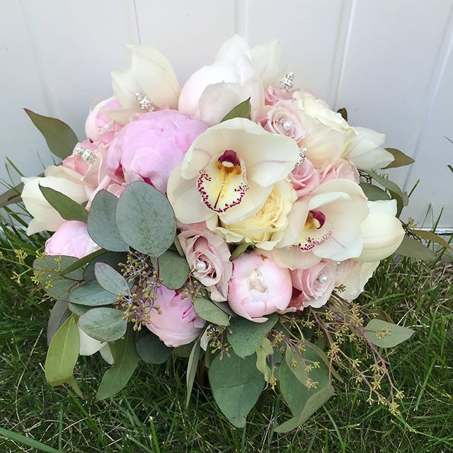 Bridal bouquet, featuring peonies, orchids, David Austin roses, blush roses & seed eucalyptus with an added touch pearl pins. #bridalbouquet #weddingbouquetideas #roses #cymbidiumorchids #pearls