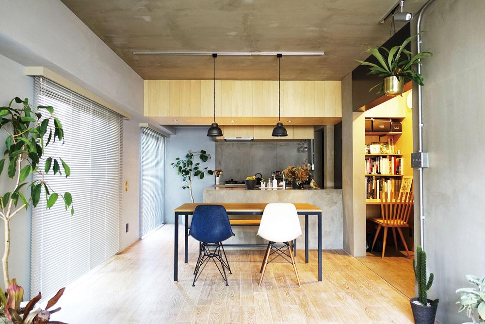 LDK と右の廊下は黒革鉄の垂れ壁で緩く区切って。存在感のある箱のようなキッチンはオリジナル。梁は木で覆い、壁とメリハリをつけた。