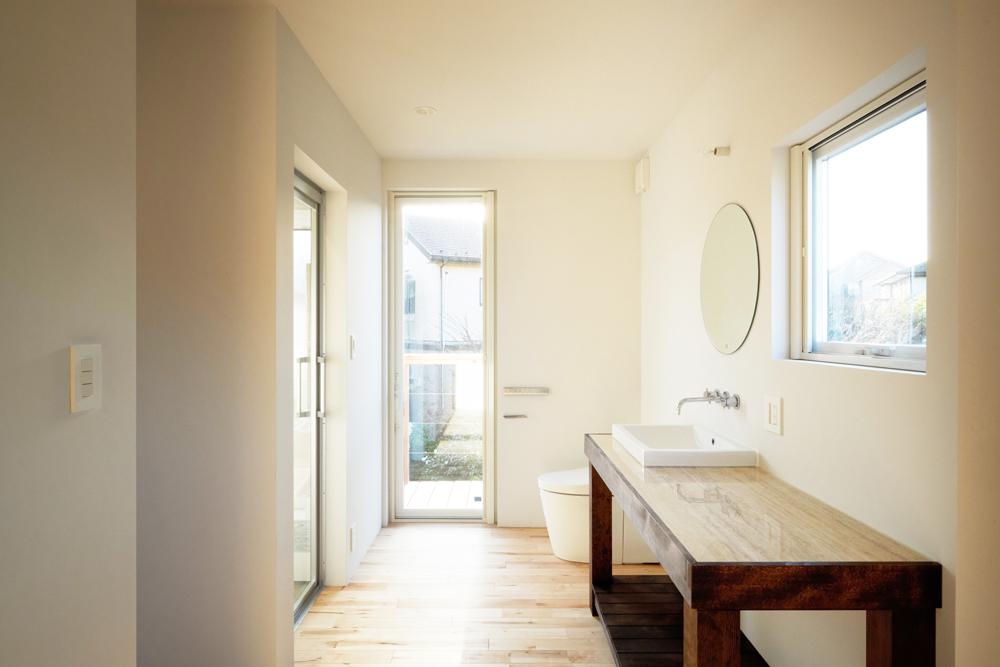 2階の洗面スペース。オープンなトイレに光が射し込む空間。