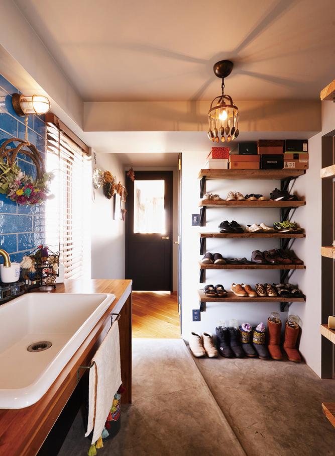 玄関には実験用シンクを使った青いタイルの洗面スペース。帰宅後すぐ手洗いできて便利だ。