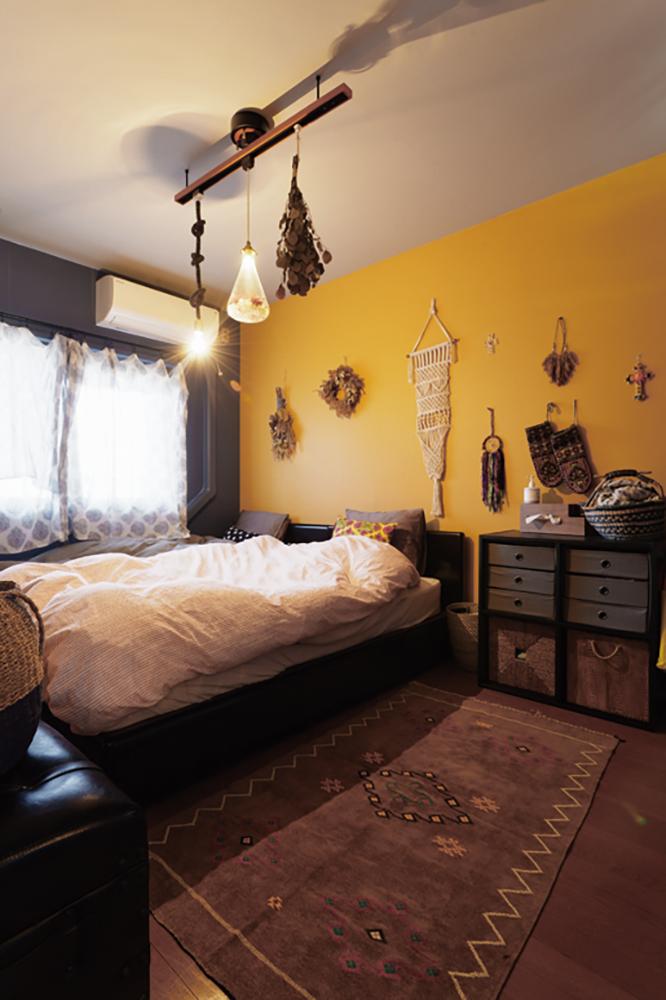 寝室は、落ち着いたイエローの壁紙に海外の民芸品やラグなど手仕事の温もりを組み合わせて。