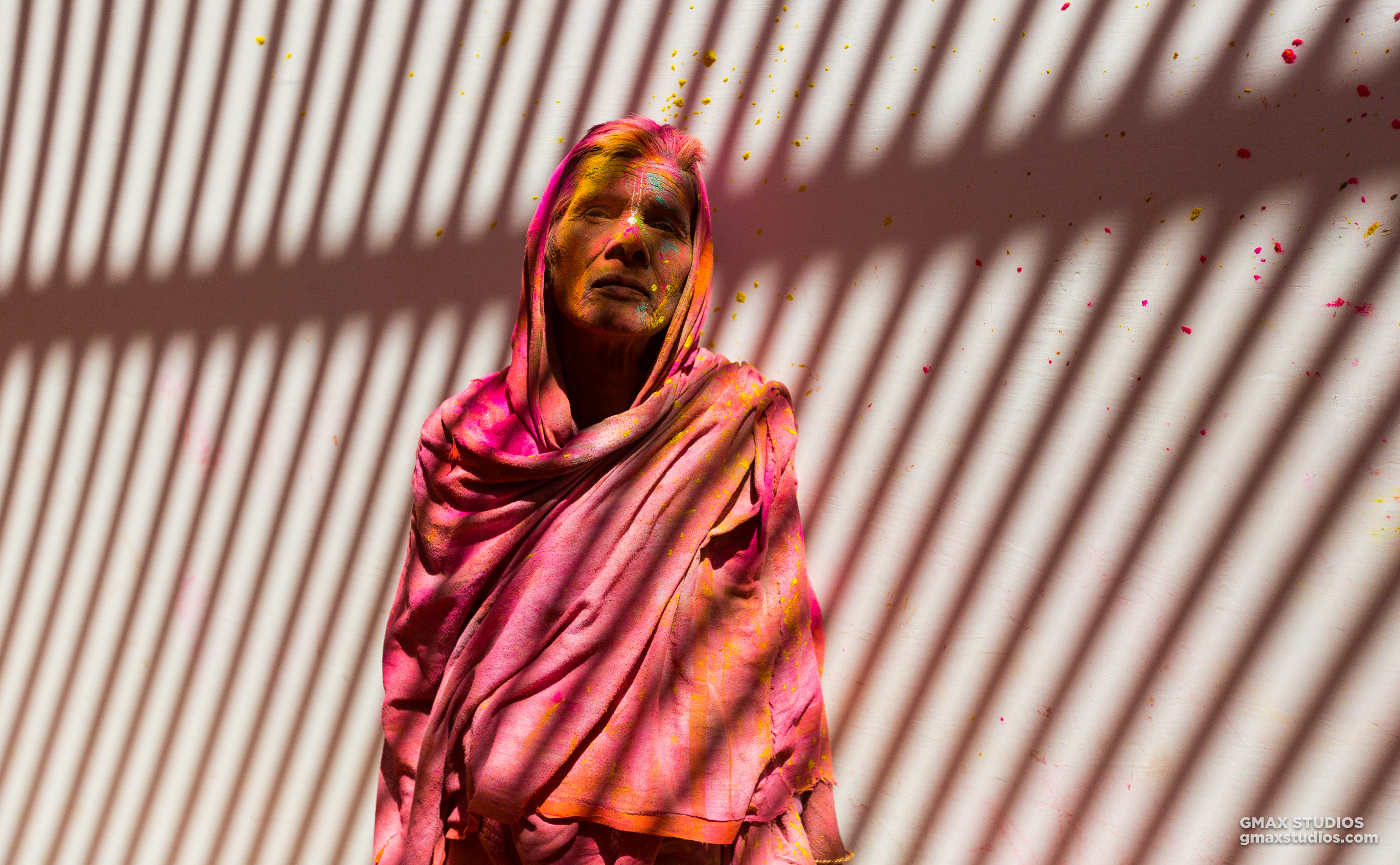 We asked the lady in the photograph if she would let us take a picture of her. She didn't respond with a yes or no but simply stood still. The photograph is an indicator of the love Vrindavan widows have for humanity and what humanity has put them through.The striped pattern on the wall resembles a prison both literal and psychological, that the widows have inhabited for centuries.
