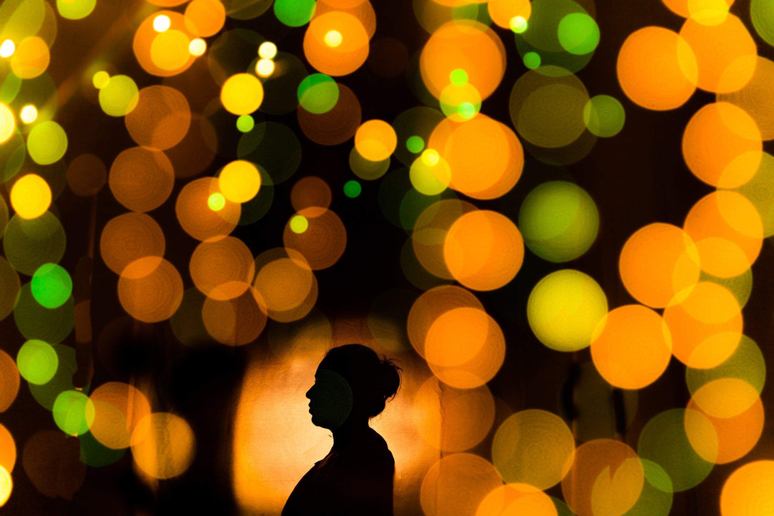 This is an in-camera multi-exposure silhouette of my wife, at home. I used  rice lights  to create the bokeh and placed a flash with a CTO gel behind my wife to create a silhouette.