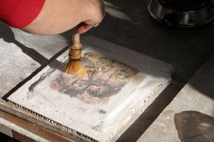 The cloth being applied with hide glue to a study piece