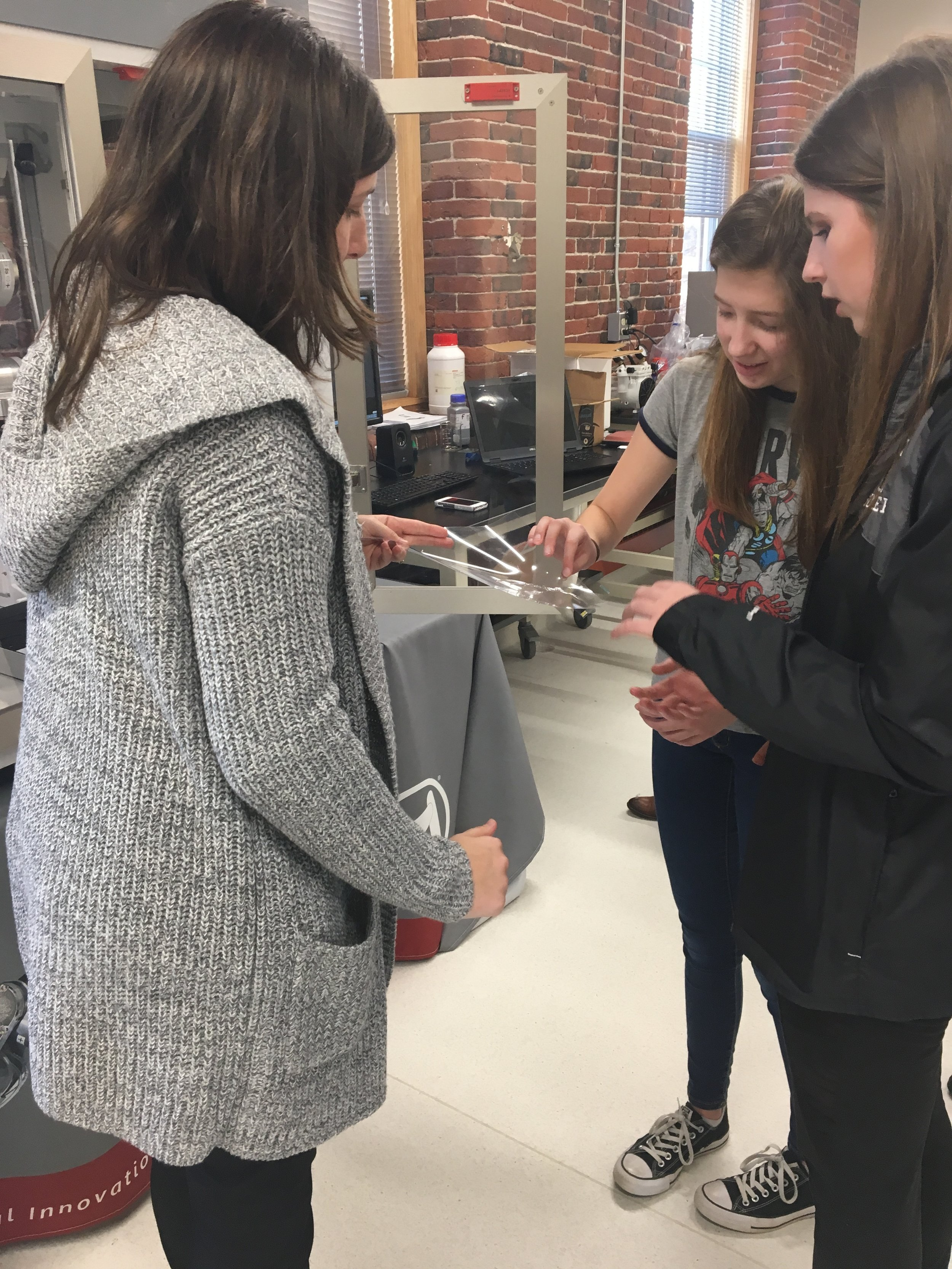 Regan and Amanda, juniors at Windham High School, feel the gelatinous structure that was printed by BioAssemblyBot®.