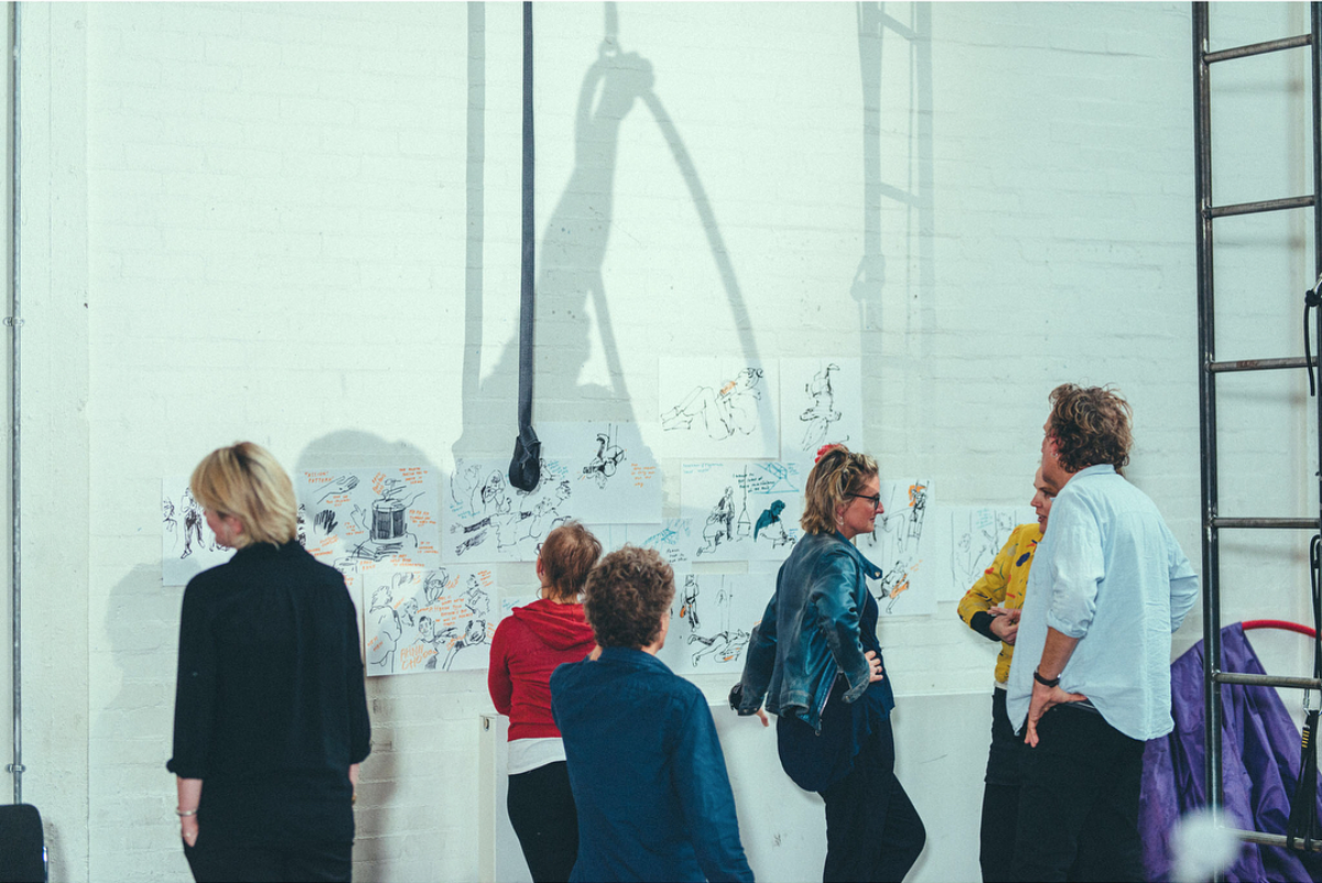 Performers and directors looking at drawings, which we put up around the rehearsal space throughout for reference. Photography by Dom Moore
