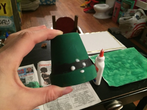 Preparing to glue gold ribbon buckle onto leprechaun hat craft