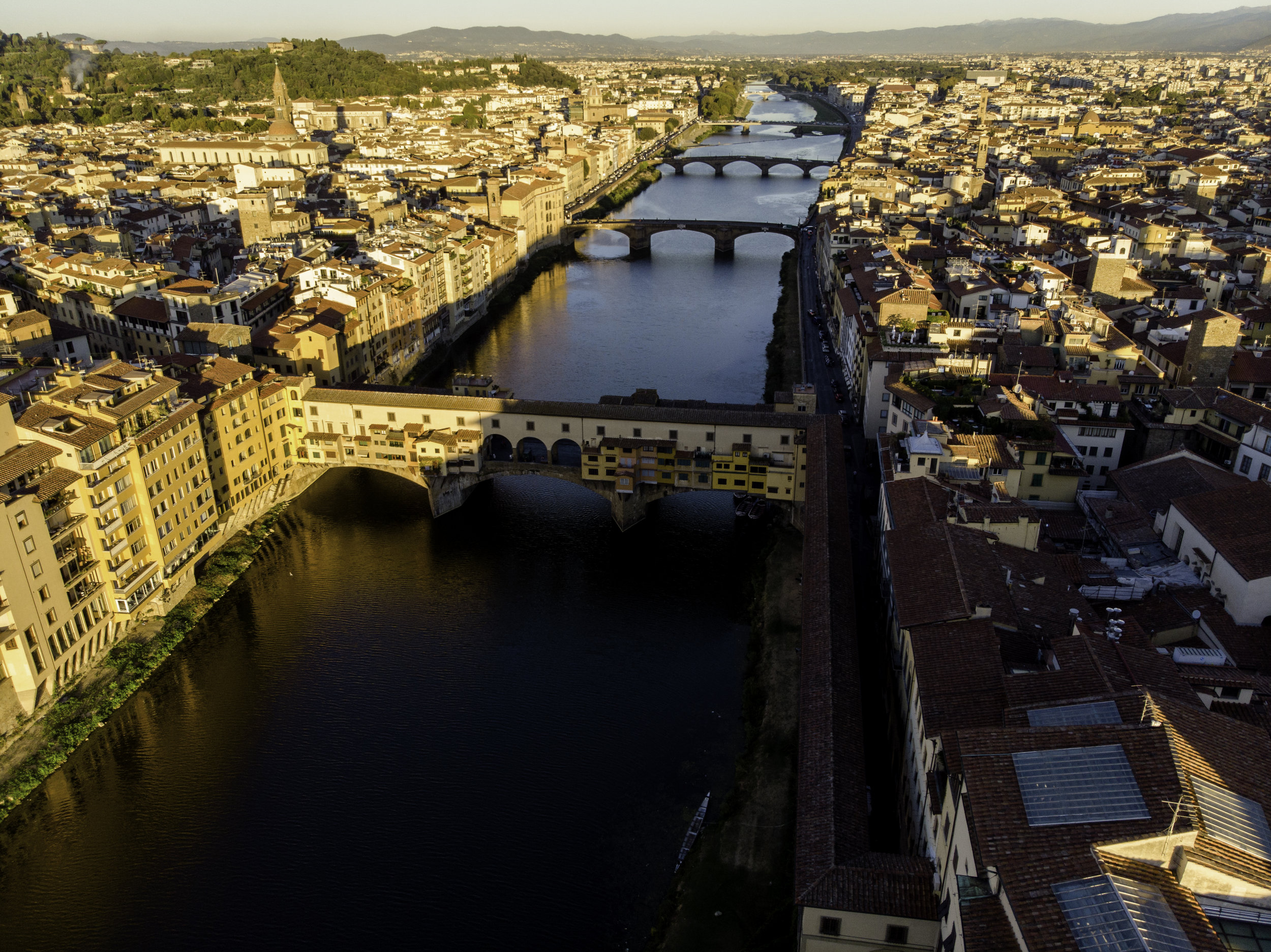 Ponte Vecchio at sunrise. This historic bridge was the only one not blown up by the Nazis as Hitler deemed it too beautiful to destroy. It is famous for its jeweler's shops appearing to hang off the sides of the bridge crossing the Arno. Photo credit: Freethedust