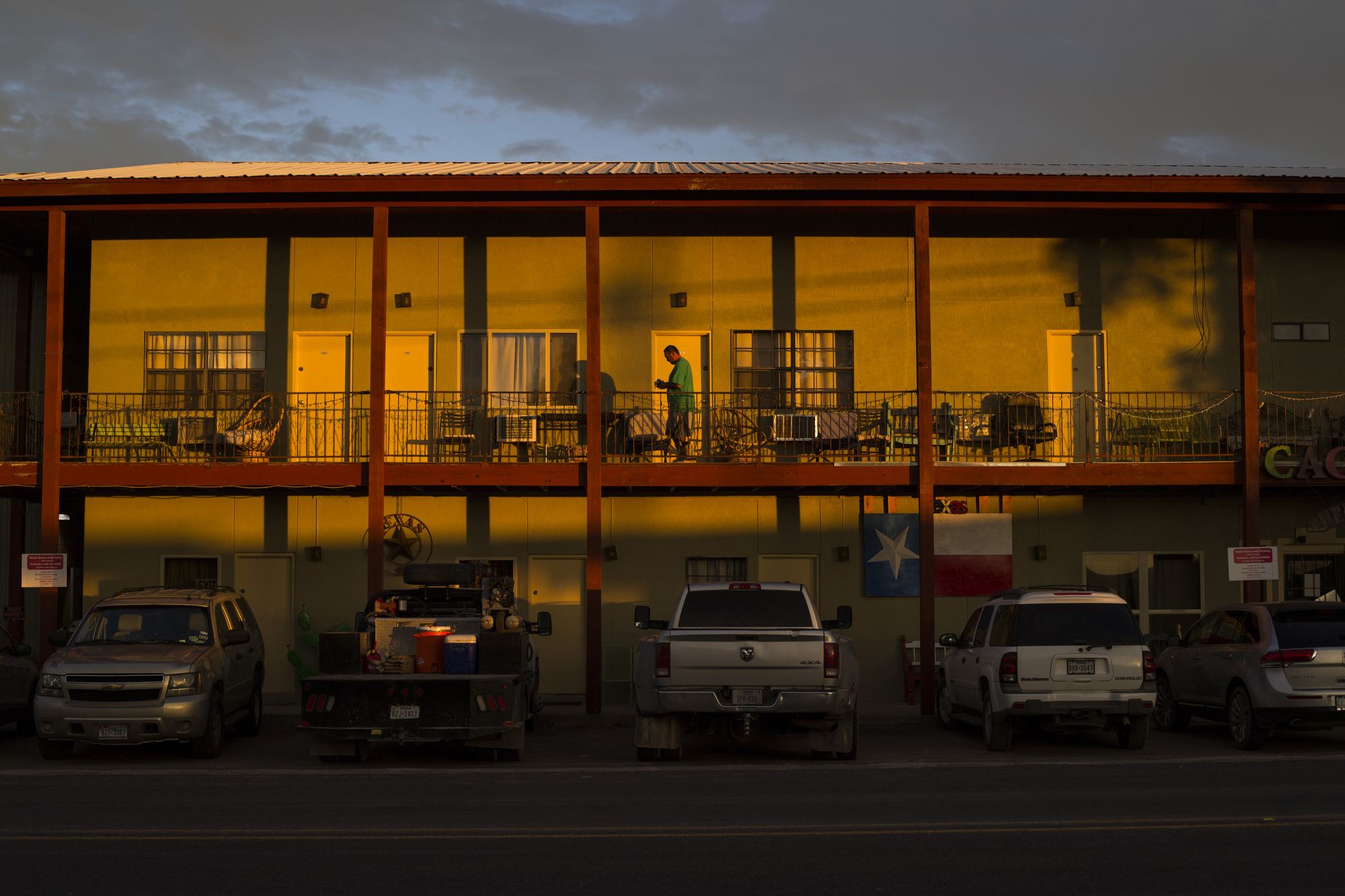 A man walks along the balcony of the Cactus Motel in Balmoreah on Wednesday, August 17, 2016. The rise of fracking nearby the town has some community members worried about their drinking water and natural springs, which serve as a popular tourism destination helping drive the town's economy.