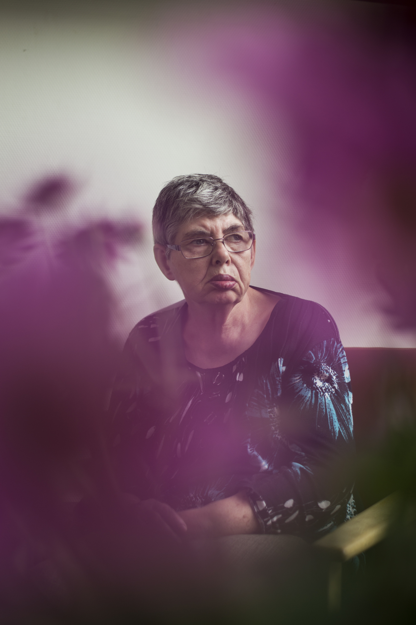 While others watch television, Anna Rosa Jacobsen sits by a window to watch the rain in her housing unit at Sølund, a mental institution, in Skanderborg, Denmark.At the age of 66, she has spent over 62 years in institutions for the mentally handicapped, moving to Sølund in 1988.