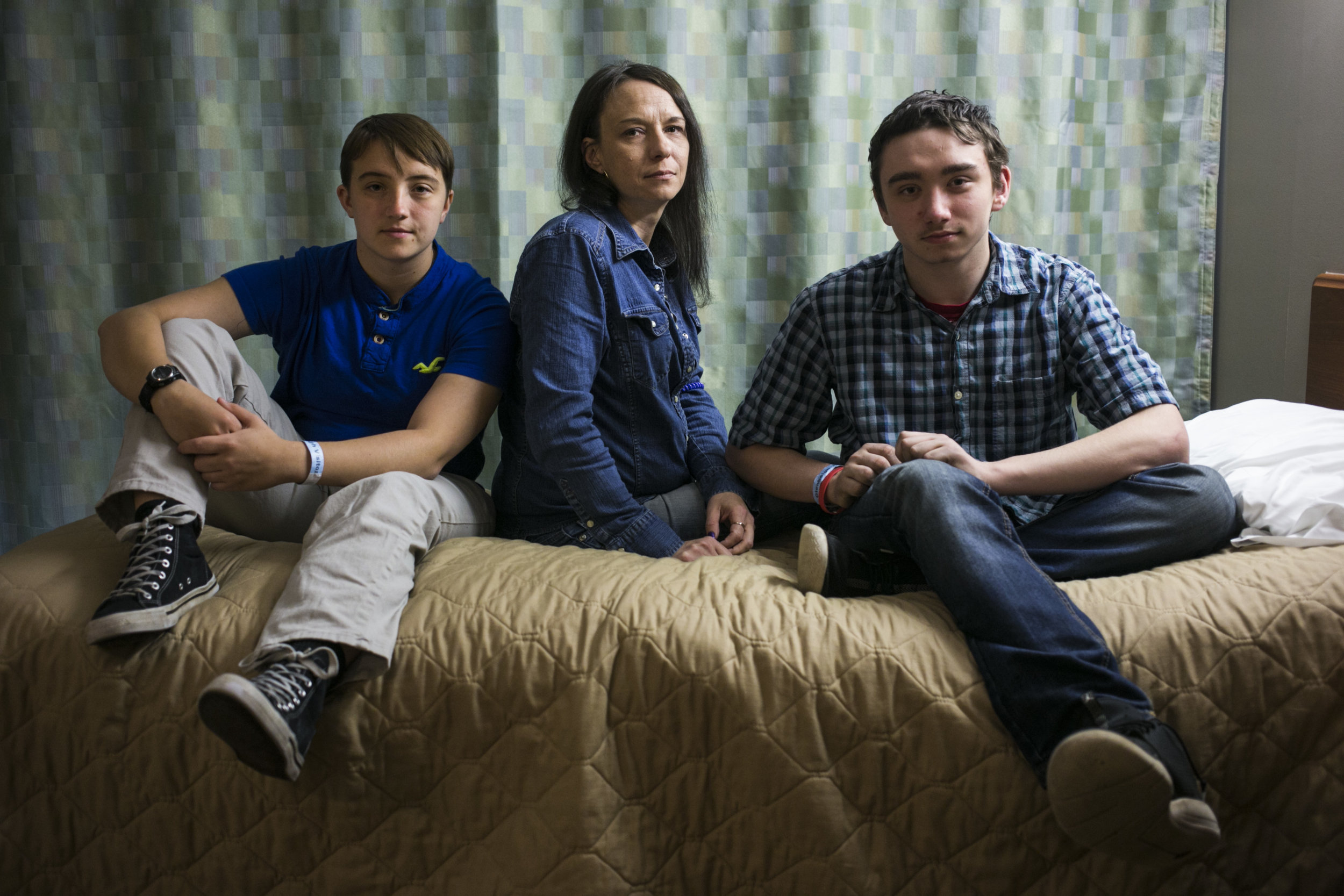 From left to right, Brianna Buie, 20, her mother Kelly McLaughlin, 41, and brother Matthew McLaughlin, 16, sit on the bed in the room where Kelly is seeking treatment at Glenbeigh, a rehabilitation center in Rock Creek, Ohio, on May 6, 2017. After a neck surgery that put Kelly on Vicodin, she became addicted to opioids and eventually heroine that left Matthew in the difficult position of self-managing his diabetes. Now, Kelly has hopes that the treatment will work despite previously failed detox experiences. For Mother Jones.