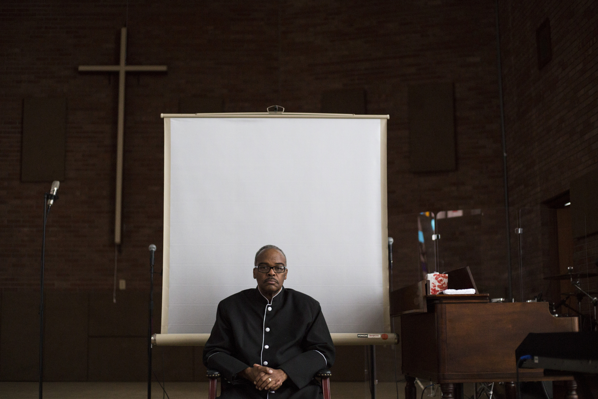 """Pastor Alfred Harris sits on the stage of his church, Saints of God Church, in Flint, Mich., on Thursday, March 3, 2016. Harris is an active member of the Concerned Pastors for Social Action, a group that had been active in advocating for Flint residents amidst the city's ongoing water crisis but also came under fire locally amid allegations that the group had received bottle water donations with their own congregations from the state long before news of the lead had been released. """"I'm not a politician. I'm not a scientist. All I know is this water is still poison,"""" Harris said. For The New York Times."""