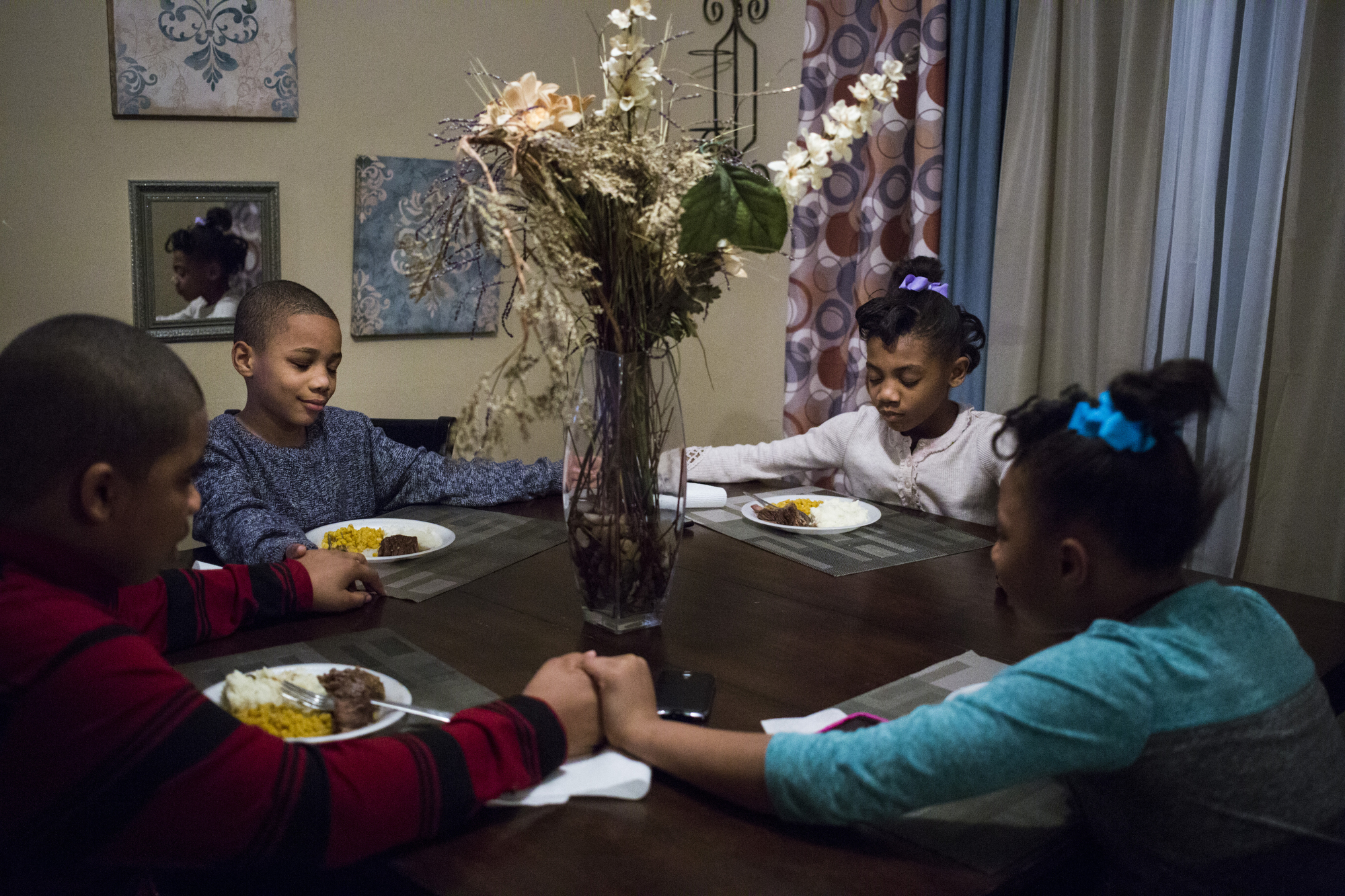 Amaria Dirrell, 8, lefts leads her siblings in prayer over their dinner, which their mother had prepared for them after a long day working as a caretaker, at their home in Flint, Michigan. The four are among six children in the home who faced elevated levels of lead in their blood amidst the city's ongoing water crisis.