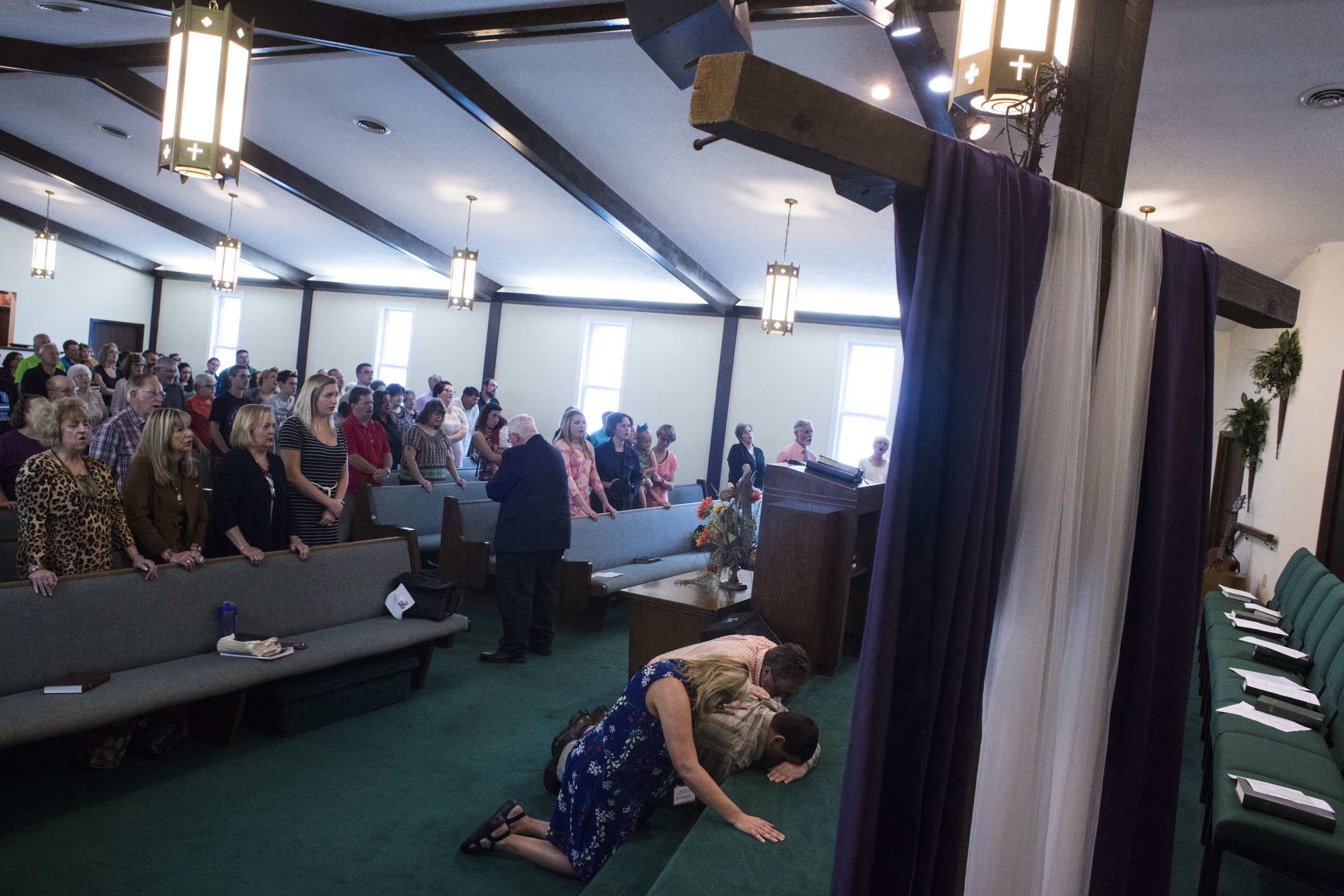 Mary Sloane, an English teacher at Floyd Central High School, prays for a member of her congregation at First Baptist Church in McDowell, Ky., on Sunday, September 24, 2017.