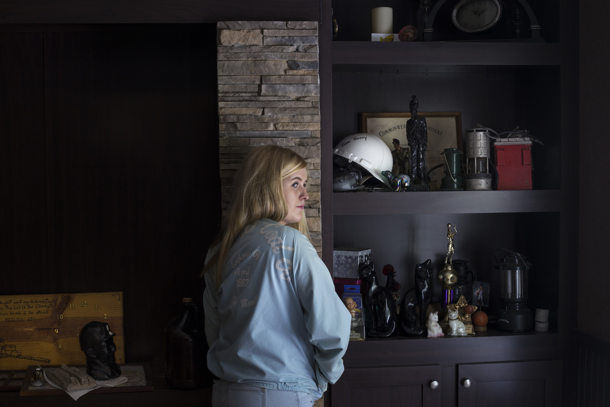 Lizzie Jones, 17, proudly wears her father's employee of the month jacket from his time working at the coal mines nearby a shelf of her family's relics of the coal industry at her home in Eastern Ky., on Sunday, September 24, 2017. Jones' father passed away from black lung in 2014. In January of 2017 her mother, who also worked in the coal mining industry, passed away. Jones said she has plans on moving into the home they once shared and has developed a complex relationship with the coal industry that both built her community stole her parent's life.