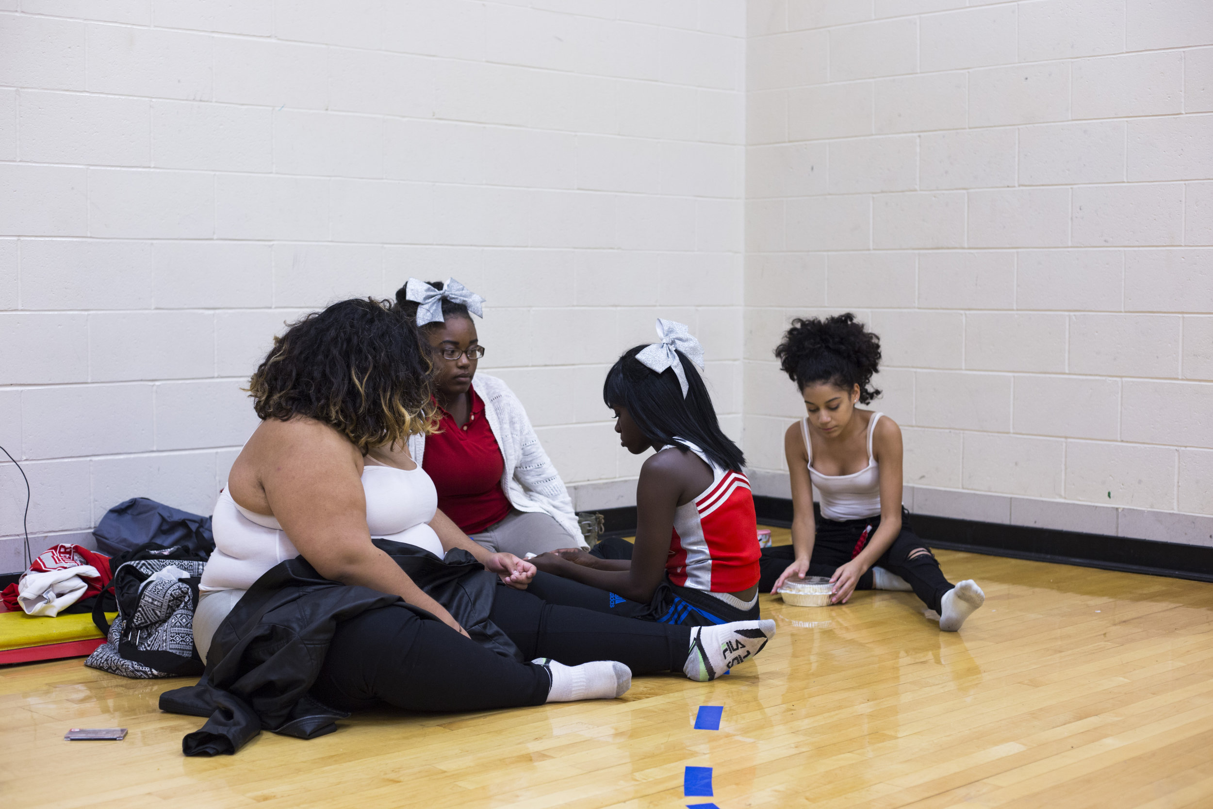 London Gladden, 17, is consoled by her friends and teammates after a boy in the hallway of the auditorium had made a remark that made her cry before cheerleading practice at the High School of Commerce in Springfield, Mass., on Friday, September, 8, 2017.