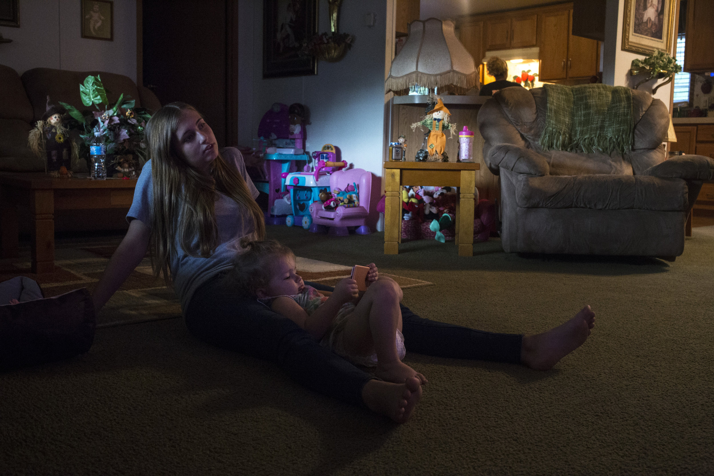 "Haley Jarvis, 17, watches ""Sing,"" a children's movie, with her daughter Paisley, 2, at her boyfriend's home in Langley, Ky., on Tuesday, September 26, 2017. Jarvis works part time at the local McDonalds and upon graduating will have to make a difficult decision for whether or not she wants to stay in the region where job opportunities have been on the decline. She said moving away to a university outside of the county would limit her access to childcare where she has support from her boyfriend's family and her own."