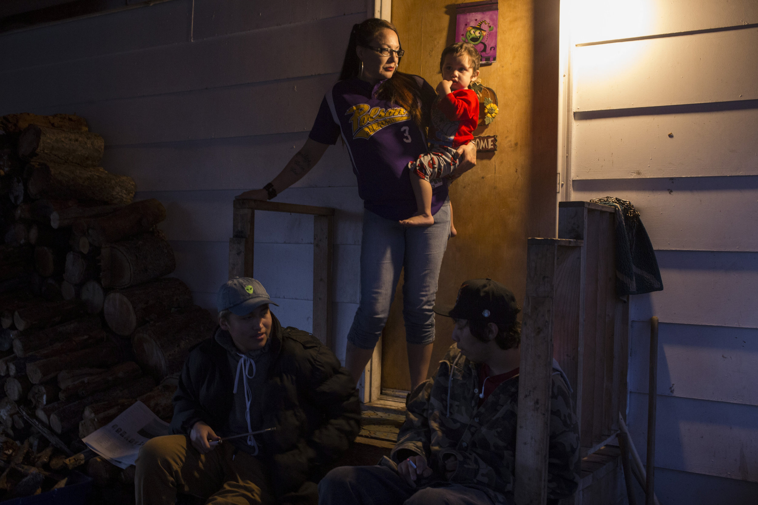 Susie Boushie, 37, looks out from her front porch while holding her grandson Niste Omeasoo, 2, as Xavier Smith, 17, and his friend Jerome hang out with Susie's son, Chris, at their home in, Pablo, Montana., on Sunday, October 22, 2017.
