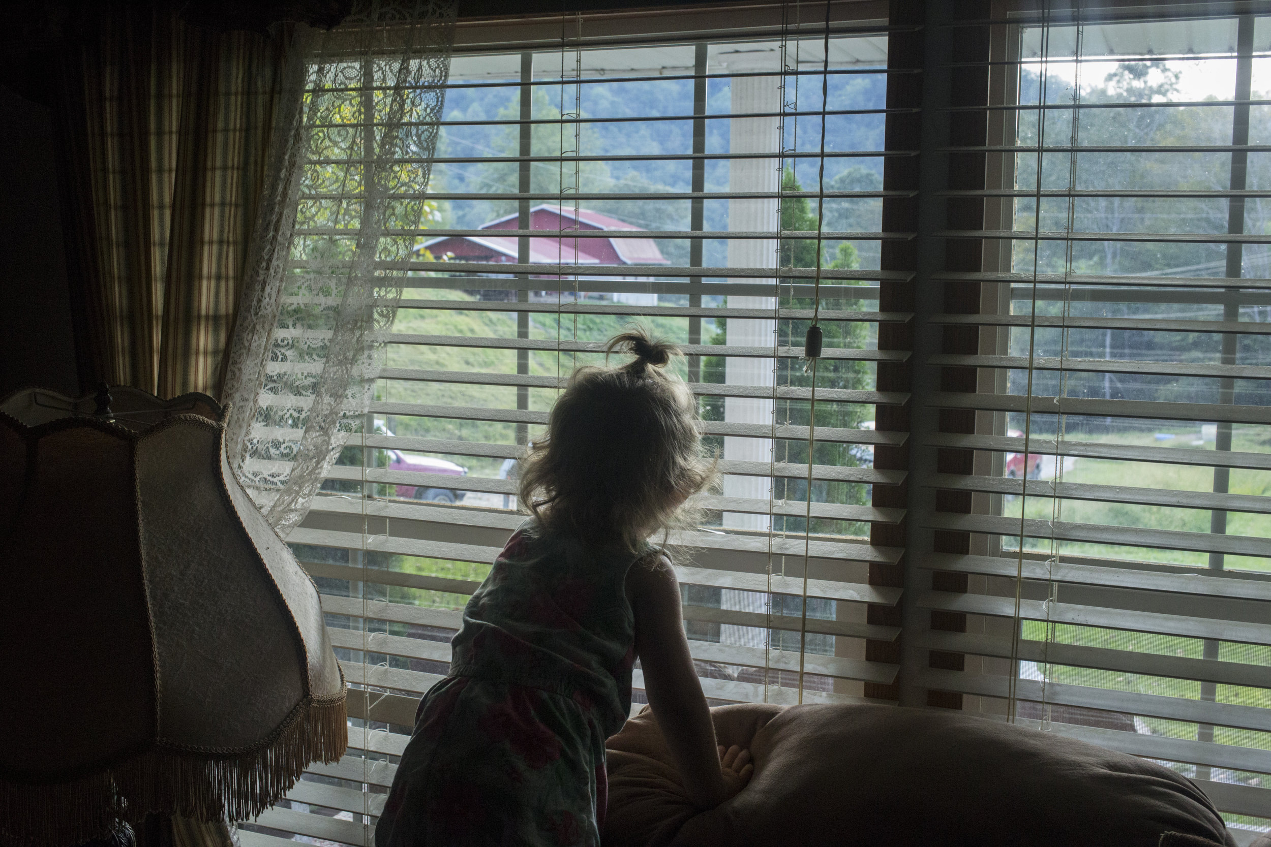 Paisley Jarvis, 2, peeks out the window of her father's living room in Langley, Ky., on Tuesday, September 26, 2017.