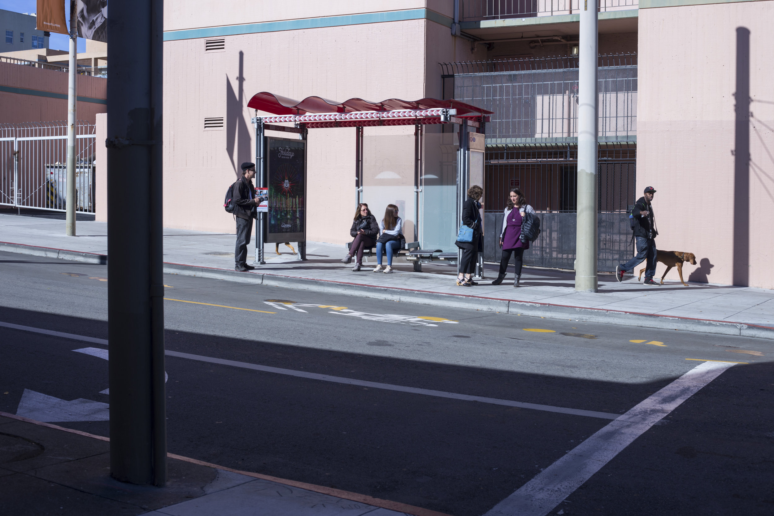 People wait for a bus in the Fillmore District of San Francisco, California., on Tuesday, November 7, 2017.