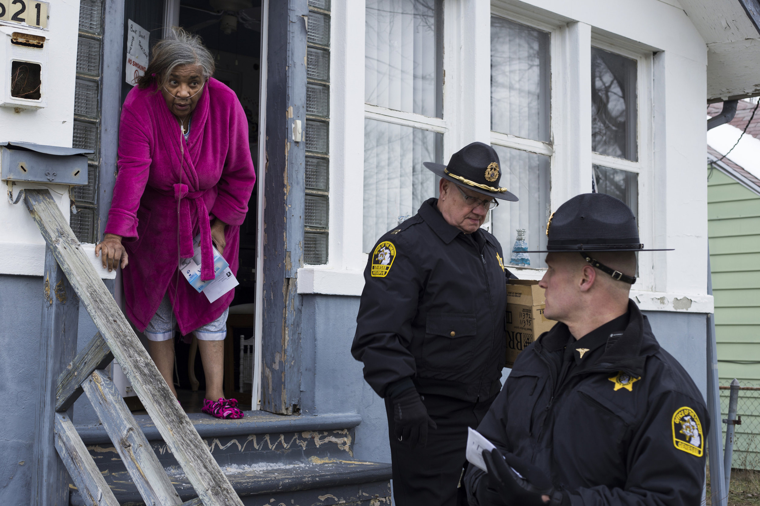 Bertha White, 64, of Flint, Mich., opens her front door to local police officers to accept a new filter and gallon jugs of water during a distribution to residents by the Genesee County sheriff's office on January 7, 2016. Distributions continued through the day on the city's north side, which is lower income, with 1,000 water filters on the service truck. A primary worry for local officials had been that the limited mobility for the elderly forced them to drink the lead tainted tap water for longer than the rest of the population. The door to door program was eventually replaced by a hotline that elderly citizens could call for water deliveries.
