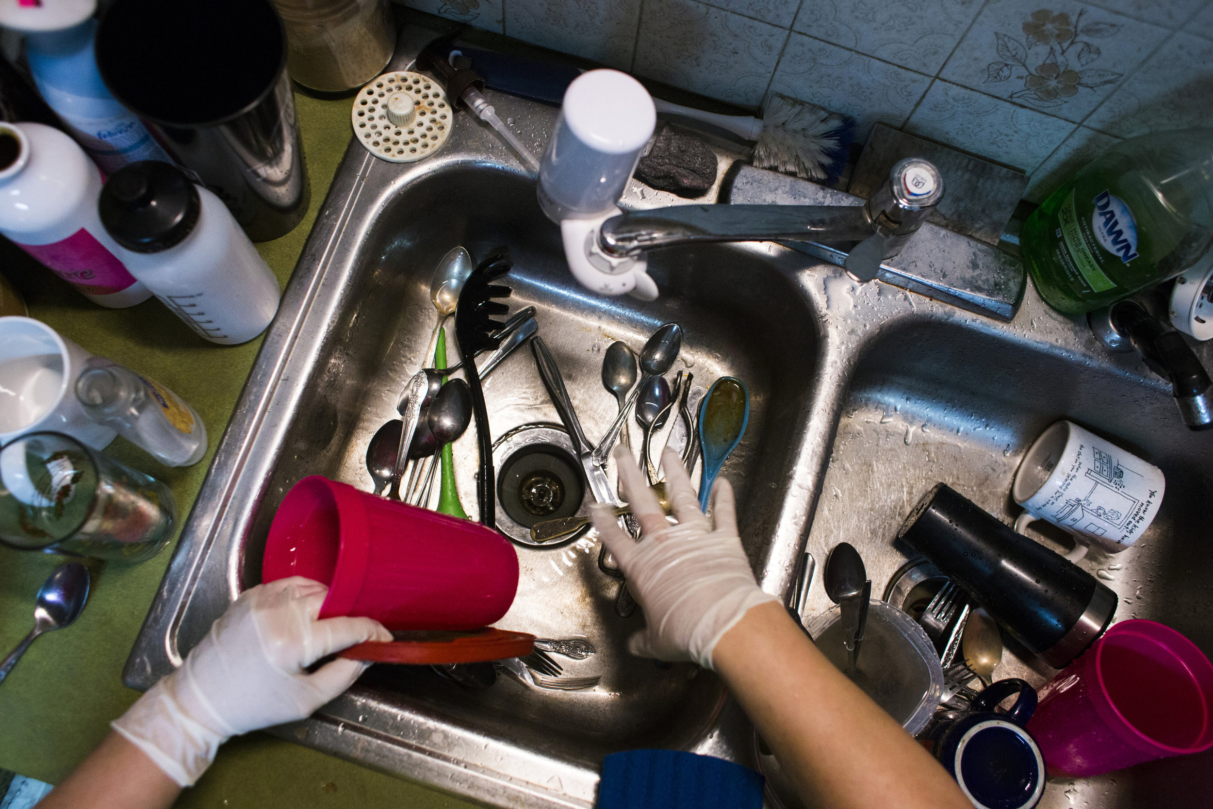 Keri Webber, of Flint, Mich., washes dishes using surgical gloves for protection on January 7, 2016. Although city officials had declared the water safe to bathe in and wash with, Webber felt she should limit her exposure as much as possible and is still distrustful of remarks made by the city.