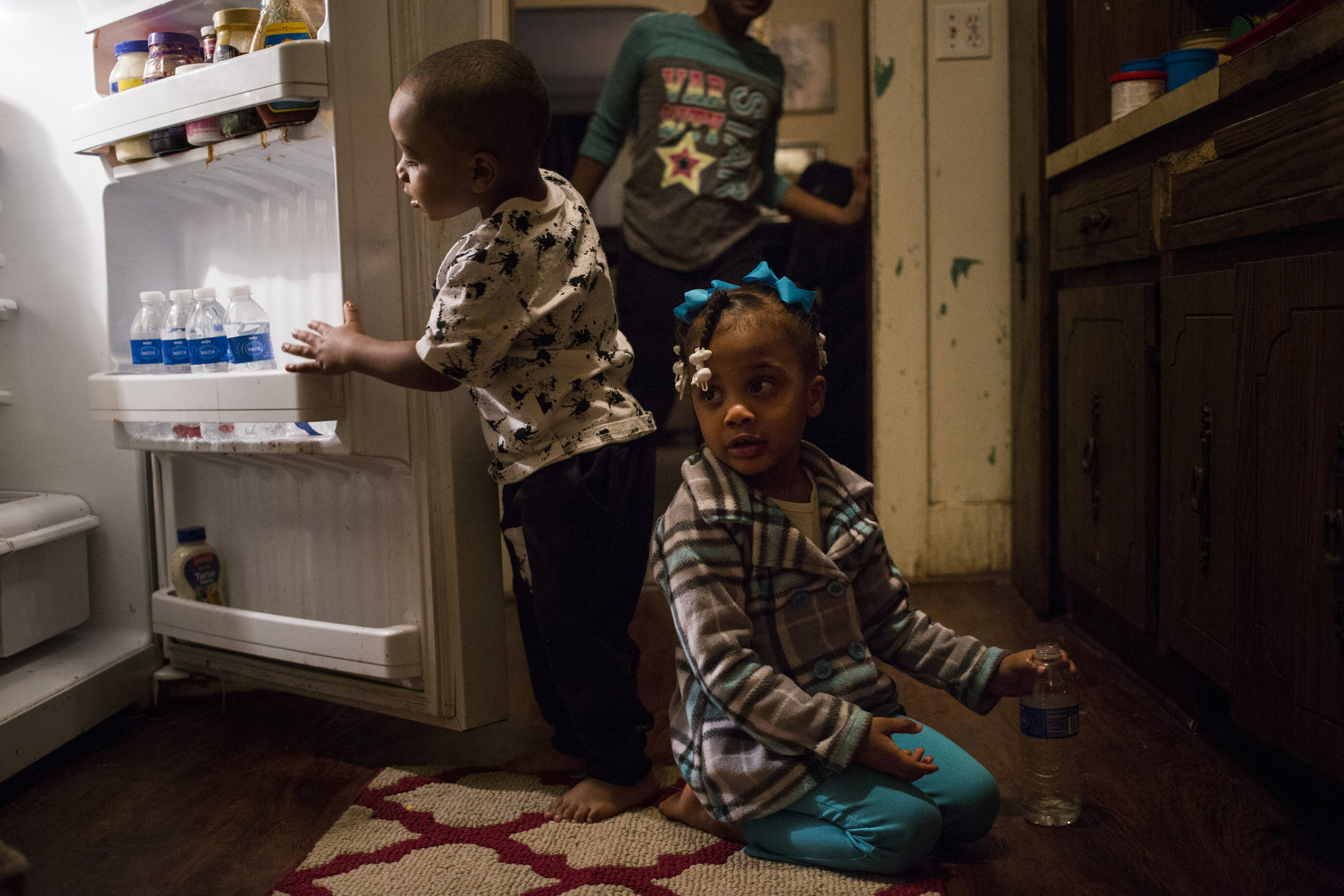 Journey Jones, 3, sits on the kitchen floor in her family's home as her brother Iveon Jones, 2, reaches for a bottled water. The pair are two of six children living in the home, all of whom have had elevated levels of lead in their blood. Their mother says she is at a loss as to what their futures hold. Iveon, she said, has already been displaying behavior issues, a common symptom of lead poisoning in children.