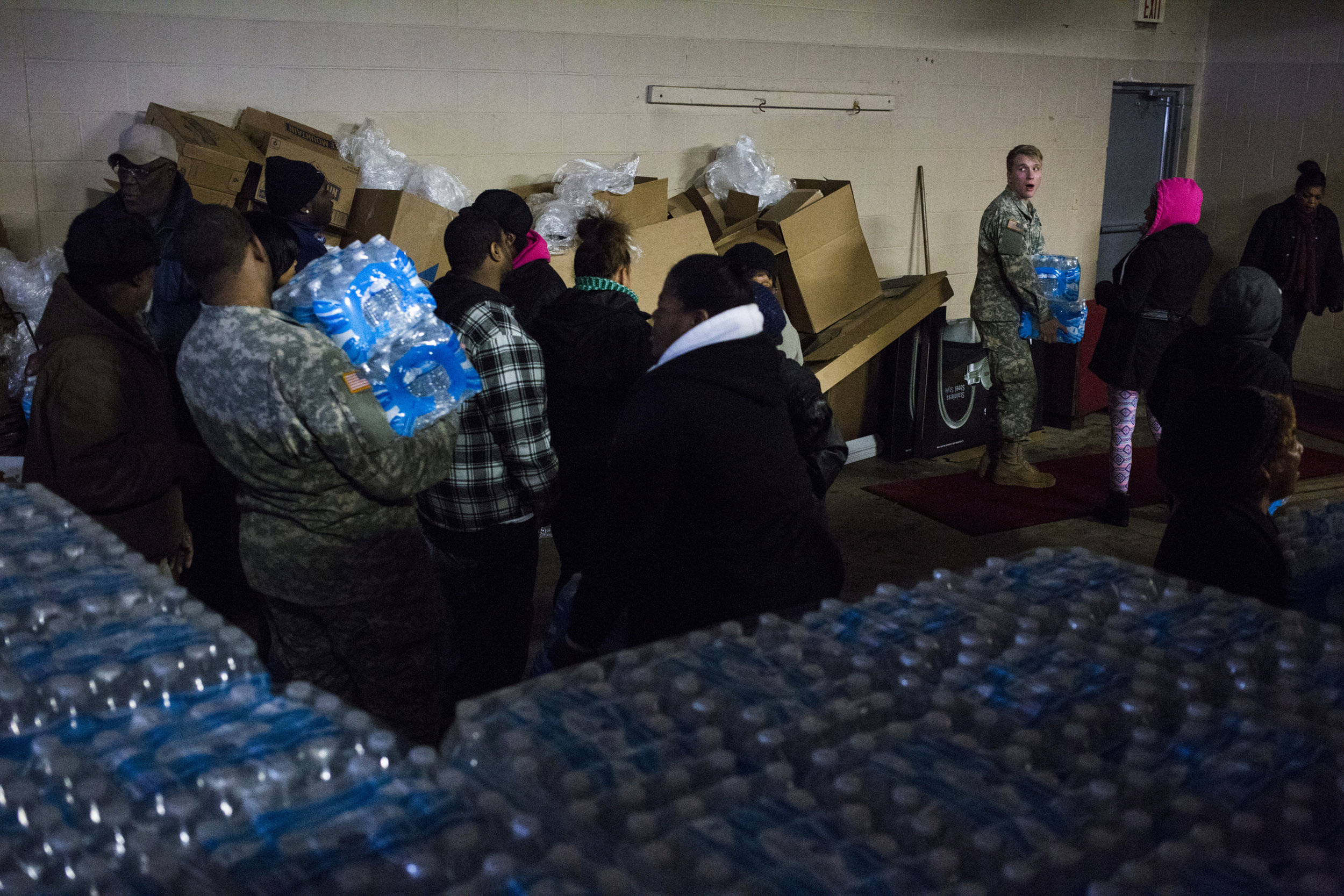A member of the Michigan National Guard gazes over his shoulder at a long line of residents form to pick up bottled water at Fire Station #3 on March 5, 2016. To the complaints of many, residents were only allotted two cases per a family at a time.
