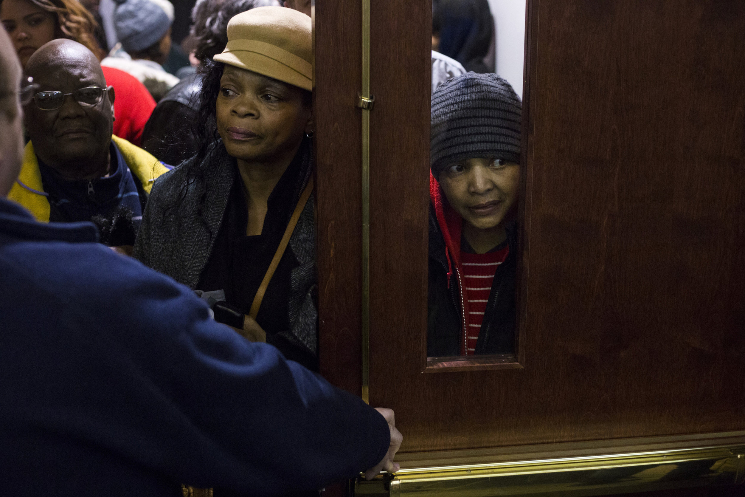 Shirley Williams, 55, of Flint, Mich., peers from a window as she and other residents are held in a nearby hallway during an informational meeting regarding personal injury lawsuits held at the Northbank Center in downtown Flint. The room, which fit nearly 400 people was over capacity within minutes.