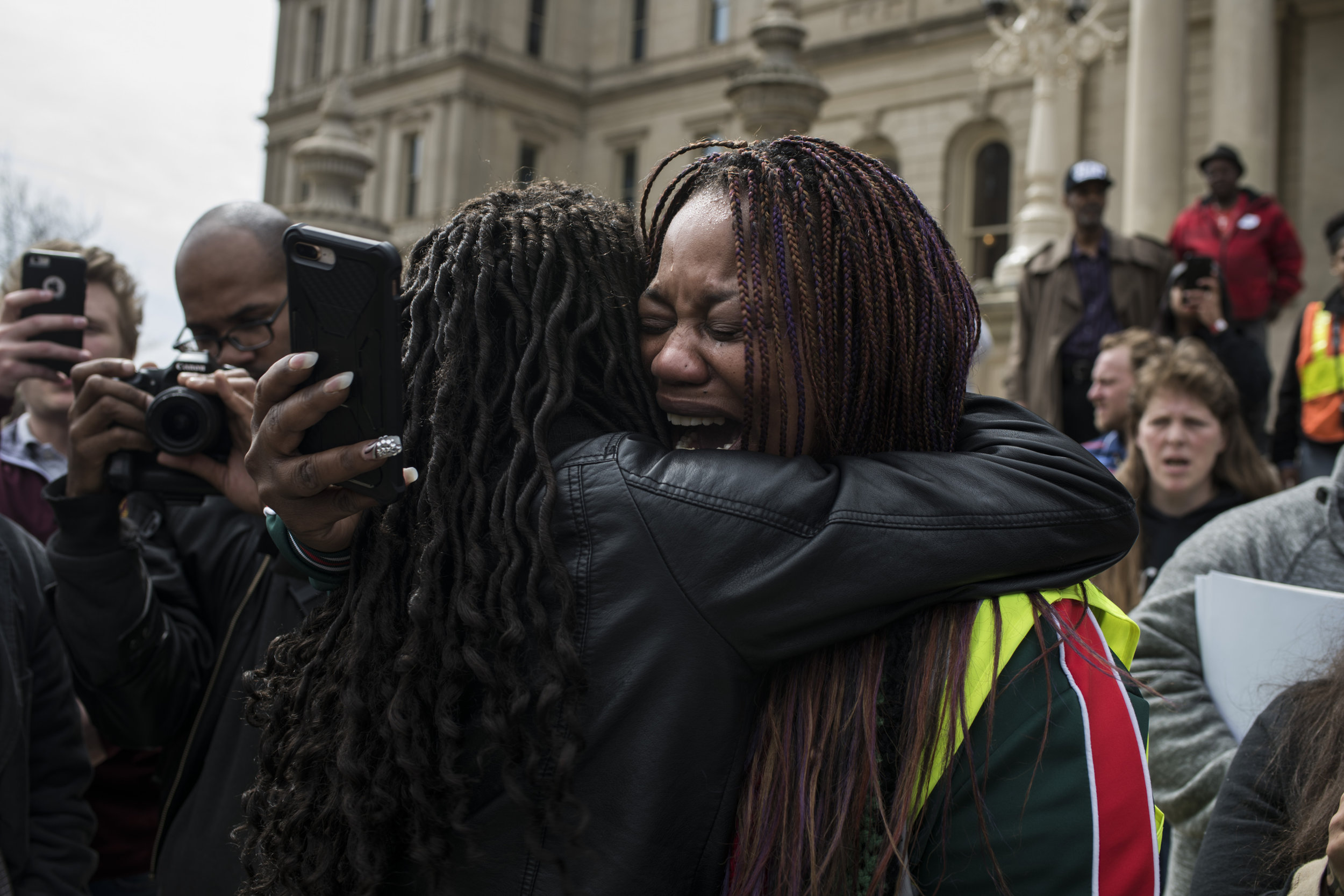 "Taywana James, 45, of Syracuse, New York, breaks down in tears following a comment from a state lawmaker during a protest at the Michigan State Capitol on April 11, 2018 in Lansing, Michigan. According to James and several protestors, the lawmaker allegedly said ""You see what they going to do to you,"" in regards to protestors being escorted out of the state legislature after they broke out into a chant. The state run water distribution sites closed in early April of 2018 after officials said the water quality is meeting federal standards."