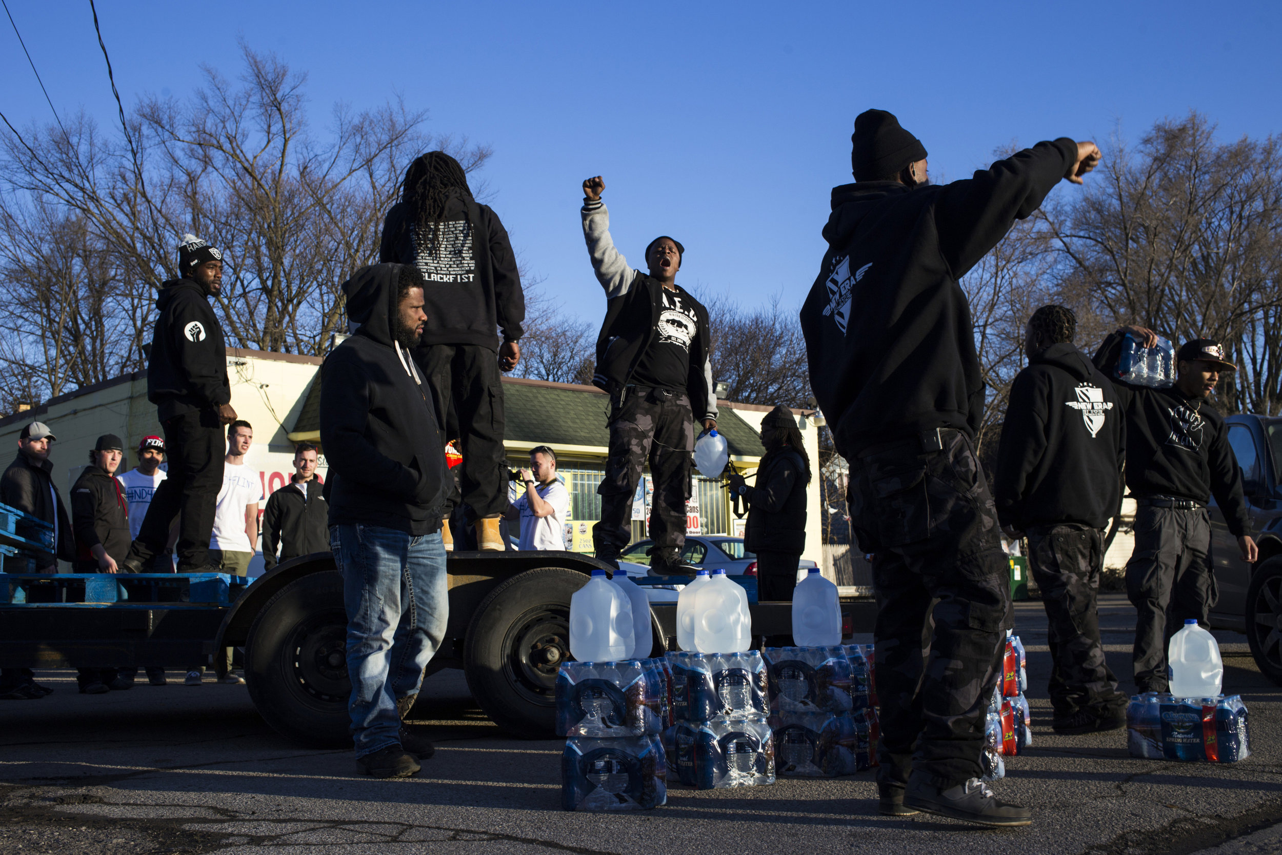 Members of New Era Detroit and friends gather and lead a chant outside of a convenient store to hand out water to Flint residents, as well as spread a message of racial equality, in Flint, Mich., on Saturday, February 20, 2016. Tensions mounted earlier when the owner of another convenient store wouldn't give business to a few members of the group, members said. Throughout Flint's water crisis, many residents begged the question whether or not it would have happened to a city that was predominately white.