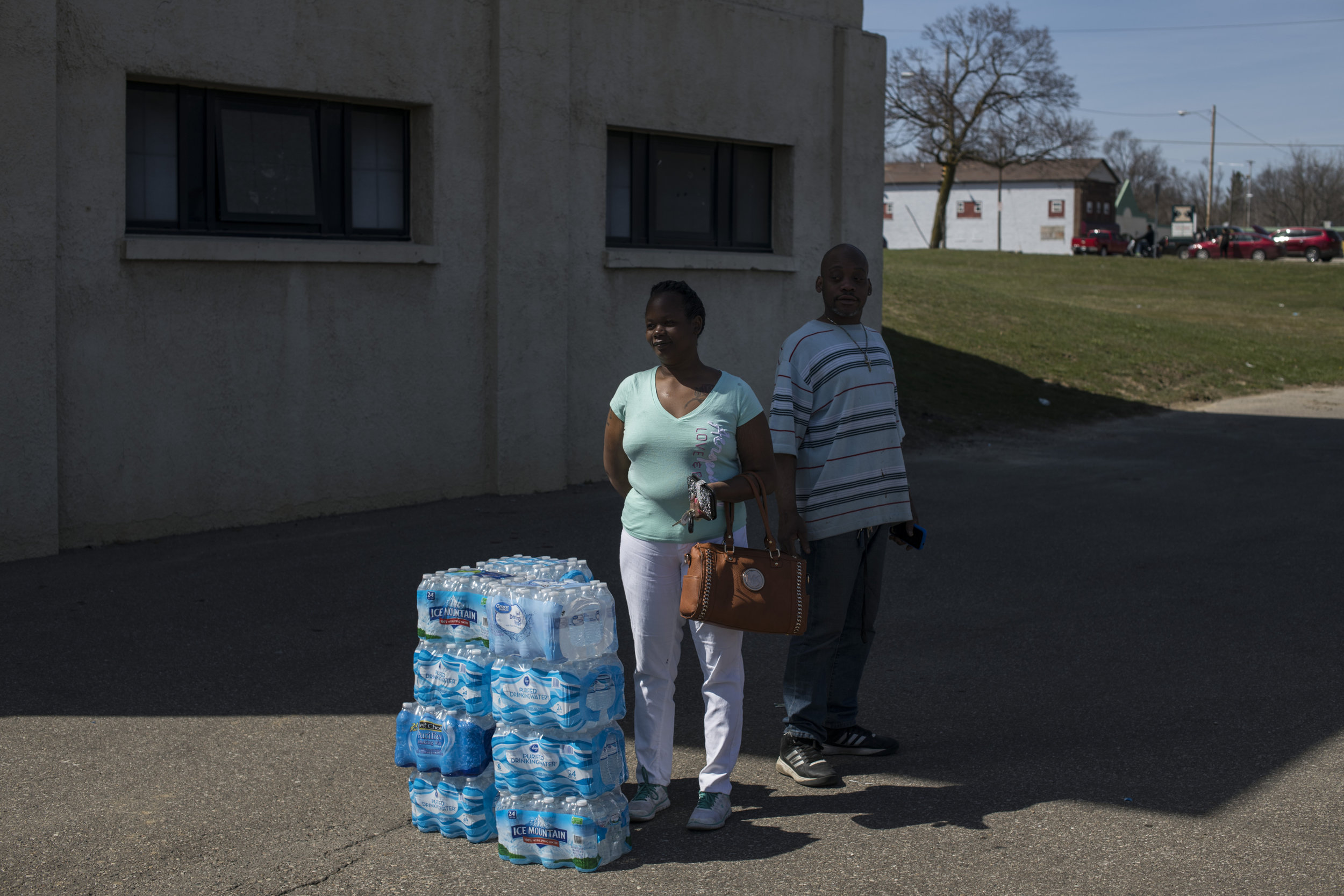 Josette Malone, 41, and Derrick Webster, 44, stand outside waiting for a ride from a friend after picking up cases of water from the Berston Field-House in Flint, on April 22, 2018. Following the closure of the state run free water distribution sites, community centers and churches stepped in to help the few residents that were able to find transit to a a very limited amount of water donations. At some sites, residents waited for over two hours to pick up cases of bottled water.