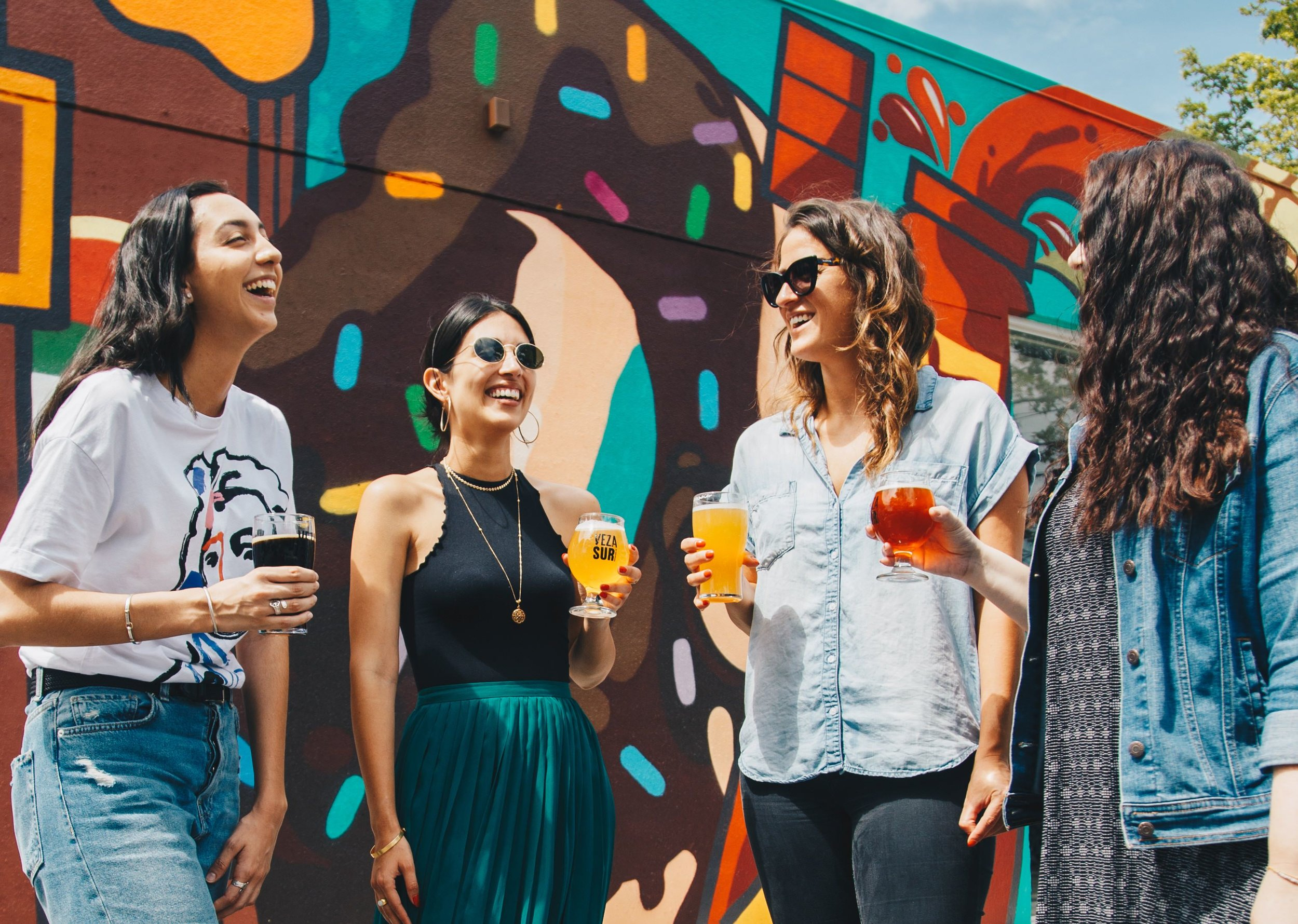 Young entrepreneurs smiling while drinking beer outside by a mural.