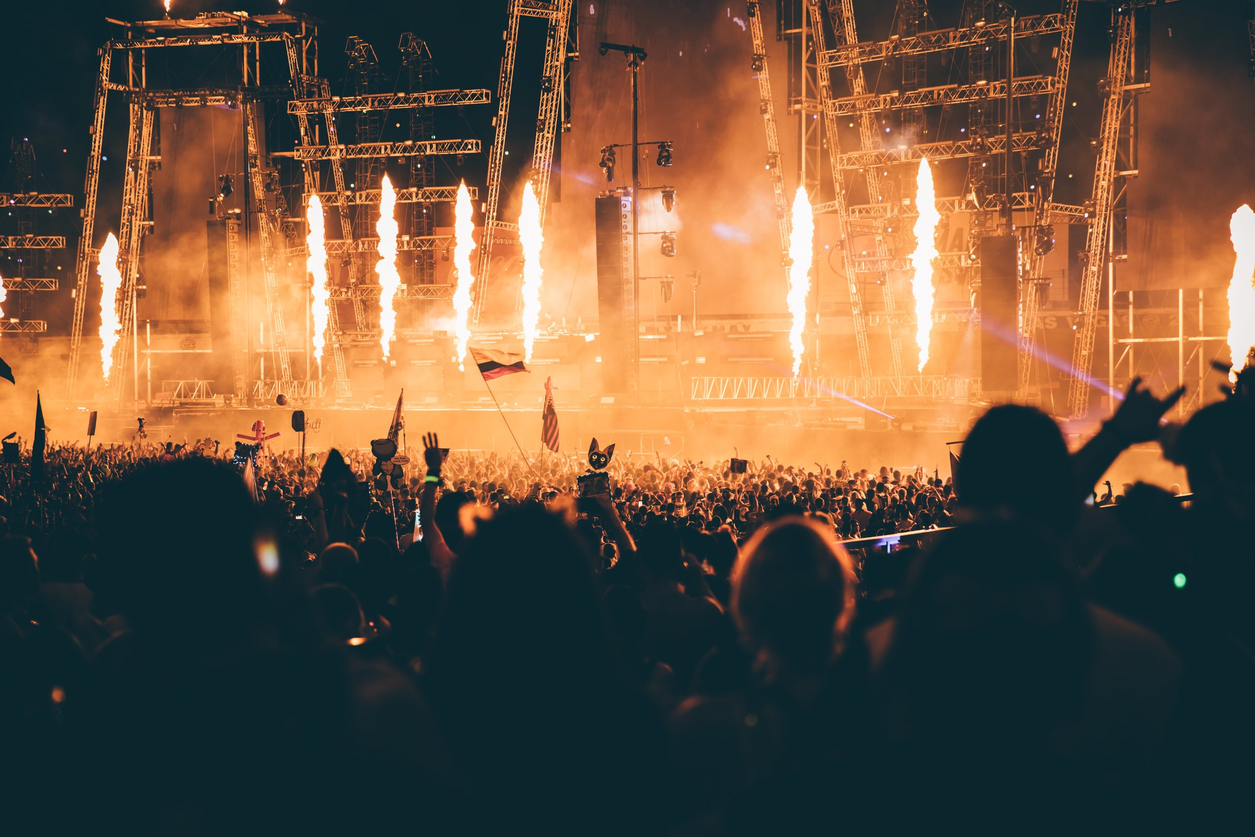 Huge crowd of people at a music festival concert with fire on stage.