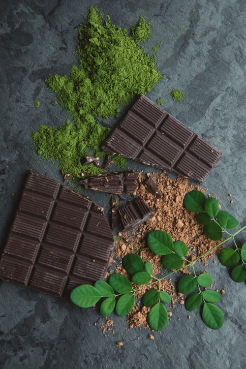 moringa powder with bars of chocolate and plant