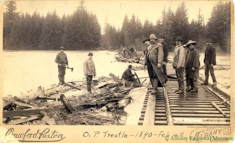 Photo of Willamette River flood dated February 4, 1890, damaged railroad track with several unknown men including Chinese workmen in coolie hats.