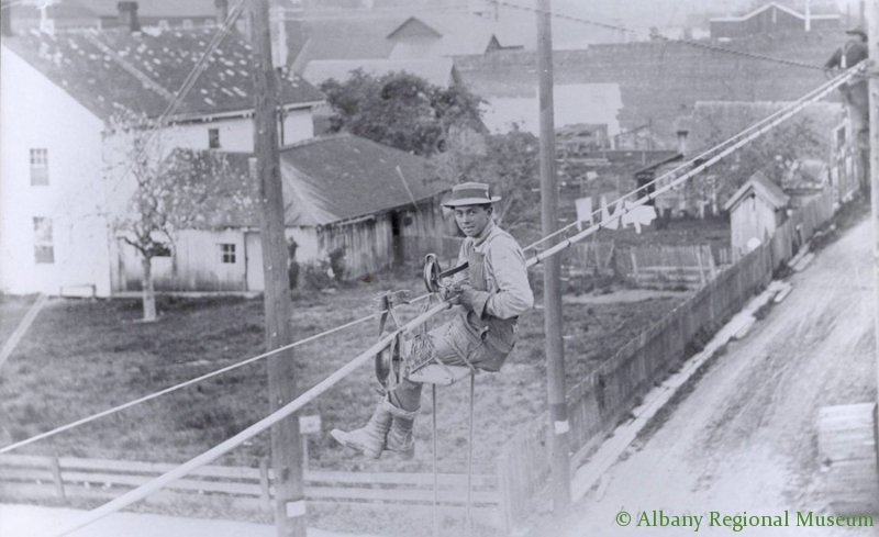 The installation of a telephone cable at Ellsworth Street and the alley north of First Avenue, c. 1900. The white building at the left was the early Demas Beach Hotel, dismantled in 1938. A young man sits on a seat hanging on the cable as he works.