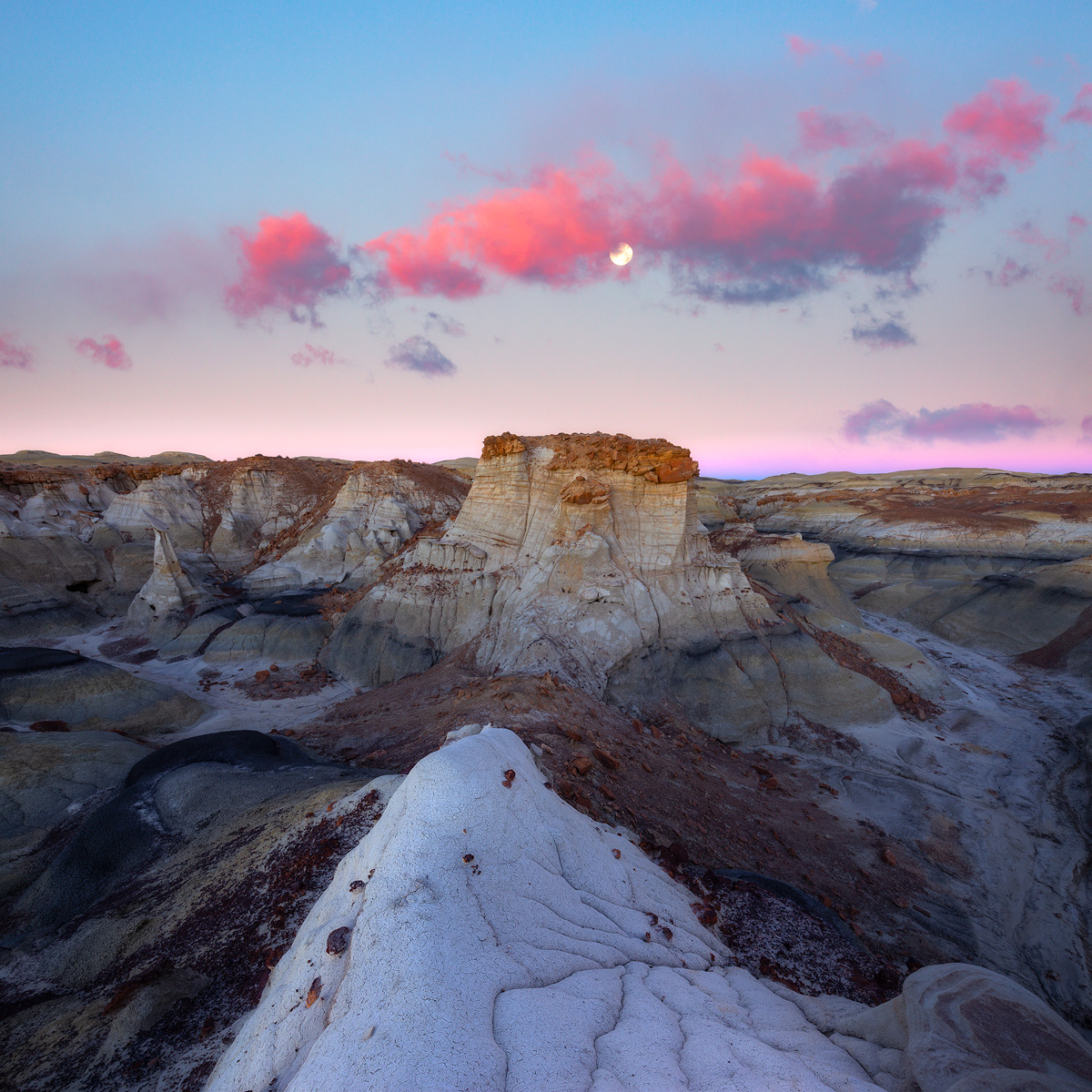 The full moon rises above the Belt of Venus deep in the Bisti Badlands of New Mexico.