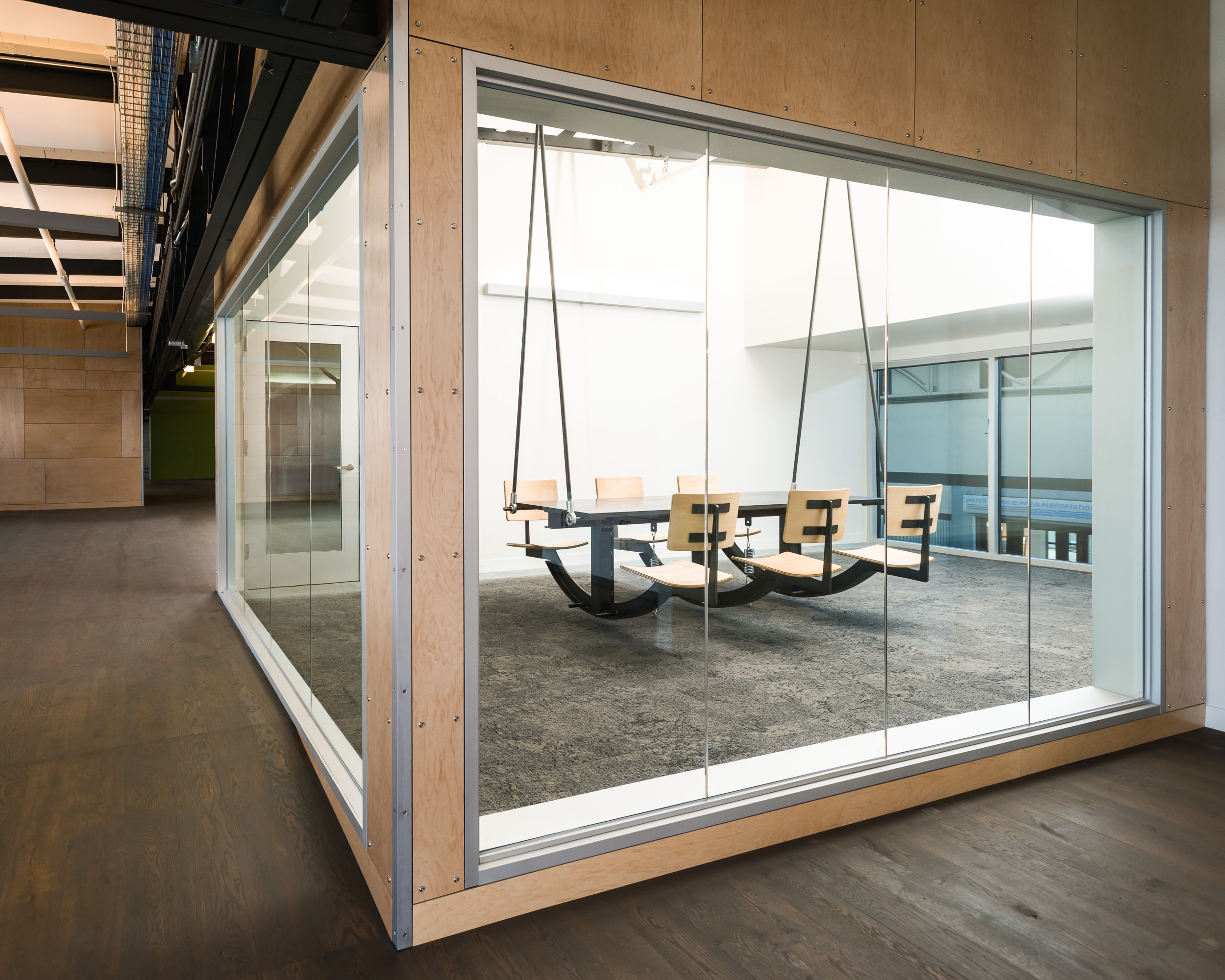 """Lundberg designed and built a swinging conference table and a reception booth for Autodesk's office in San Francisco. Based on Autodesk's request for a conference table """"emblematic of collaborative use"""", the conference table is a hanging fixture that moves with the movements of its participants, i.e. """"we're all in this together"""".  These photos document the on-site assembly process. The materials were primarily wood and blackened steel. During construction, before spring dampers were installed, staff would come periodically to """"give it a go"""".  A: Lundberg Design"""