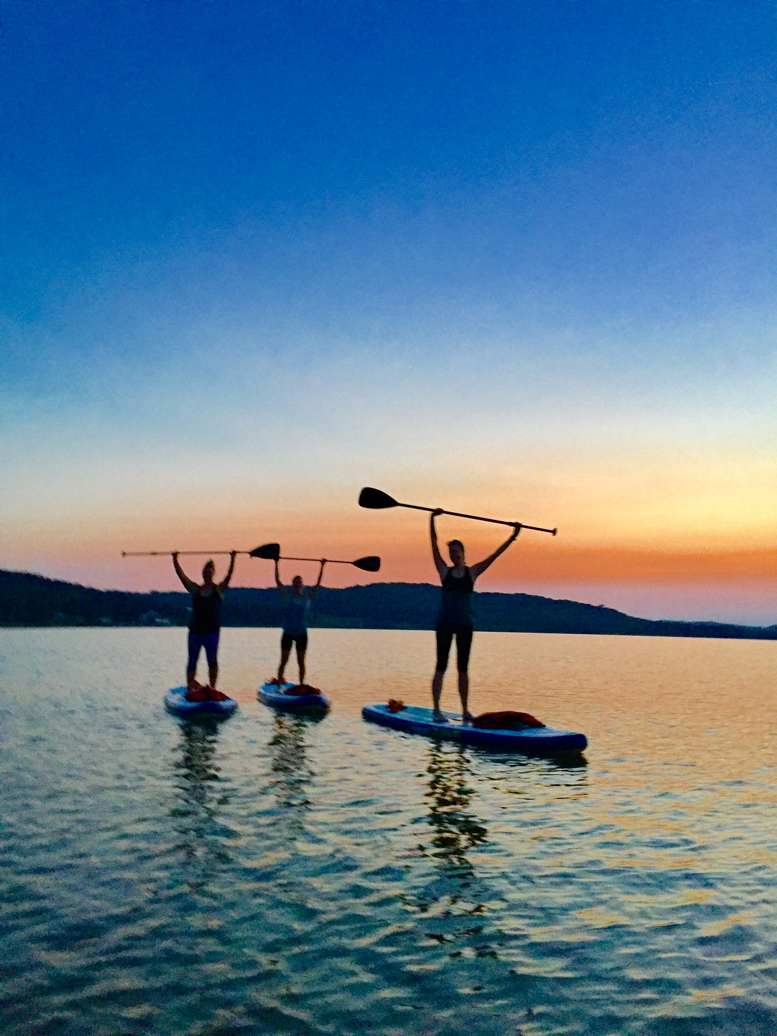Three people standing on paddleboards, silhouetted by the sunset. They're holding their paddles over their heads.