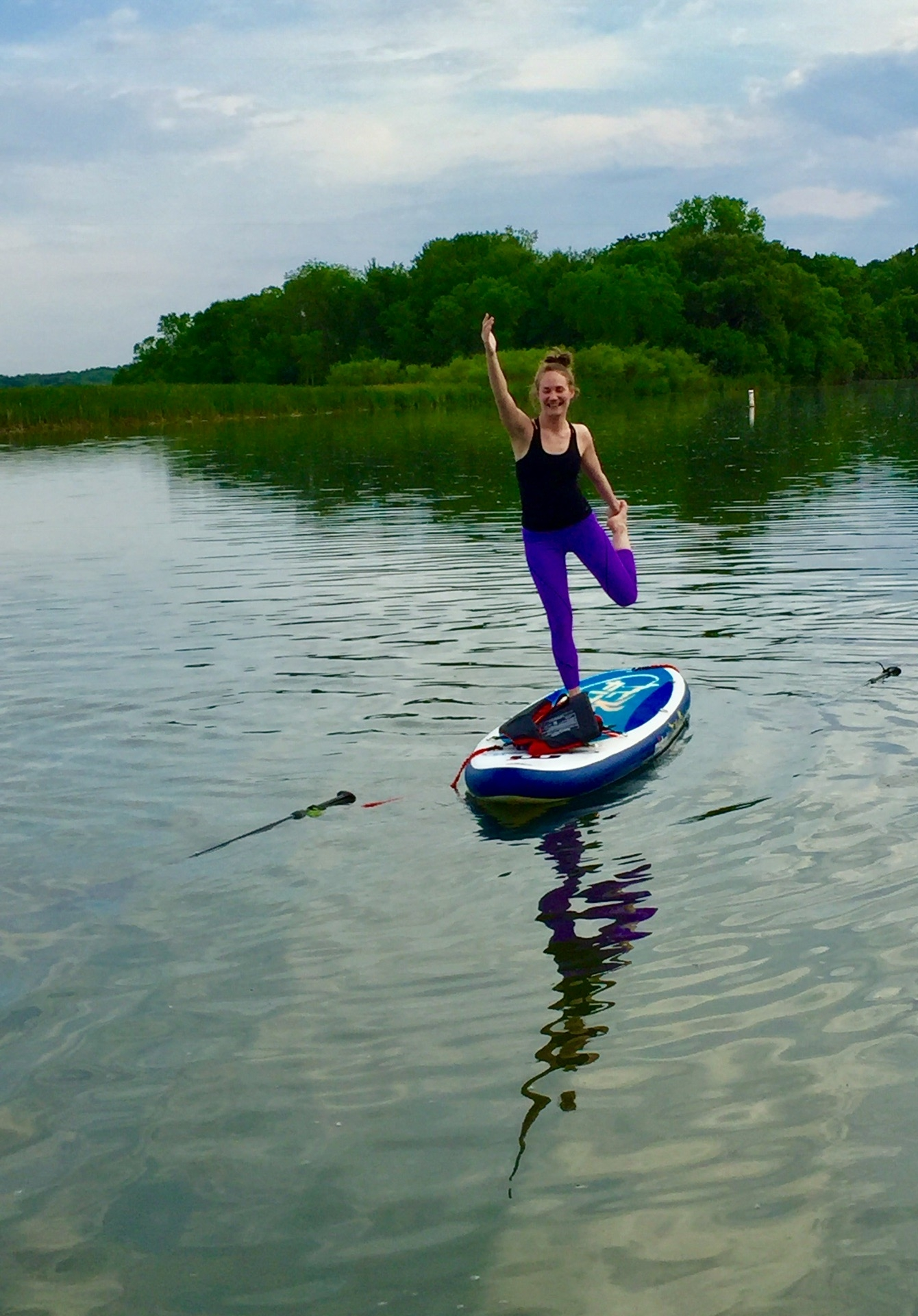 A photo of a woman doing dancer pose while standing on a paddleboard on the water.