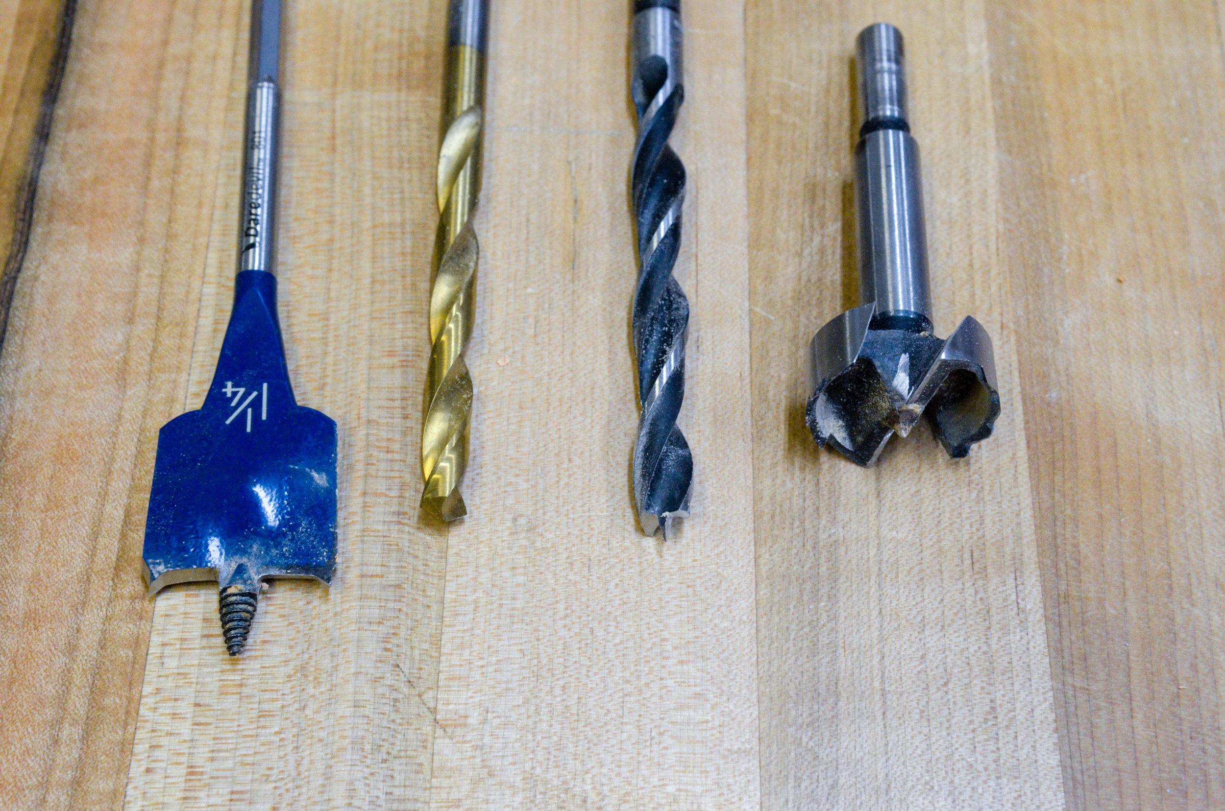 A visual comparison between a spade bit, twist bit, brad point bit, and Forstner bit (left to right).