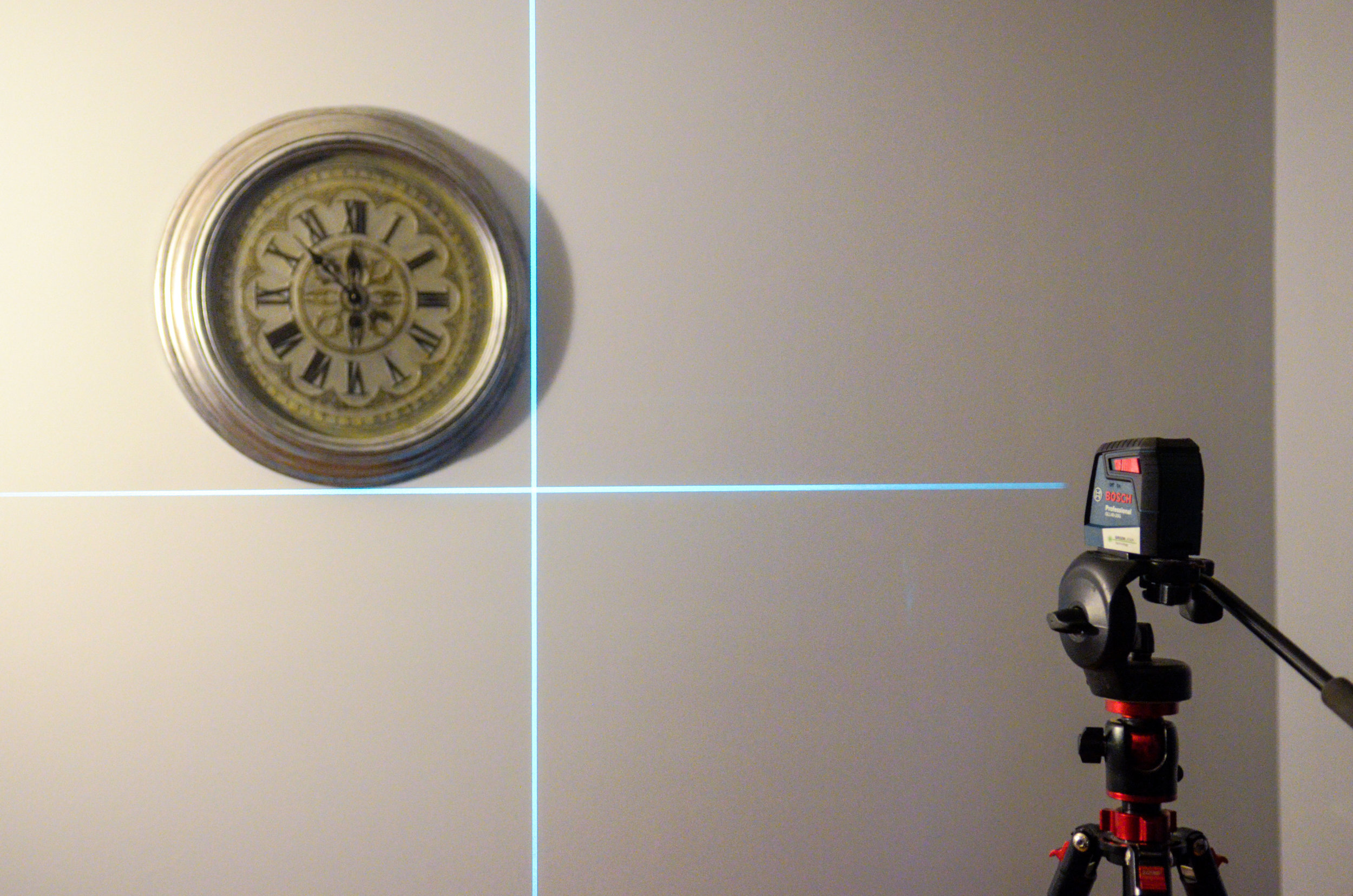 The Bosch 40-ft. cross-line level projected on a light blue wall.