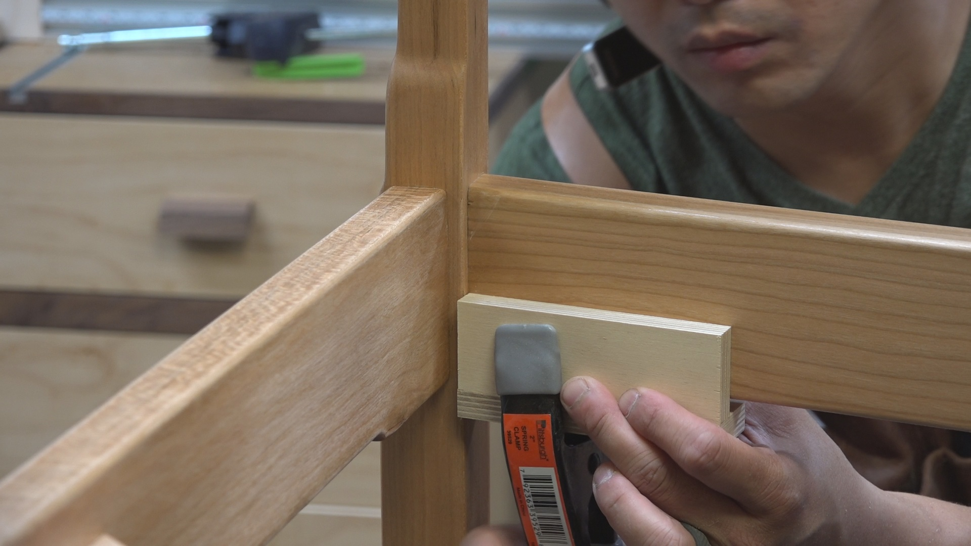 A jig and spring clamp set to the proper height to attach the corner blocks.