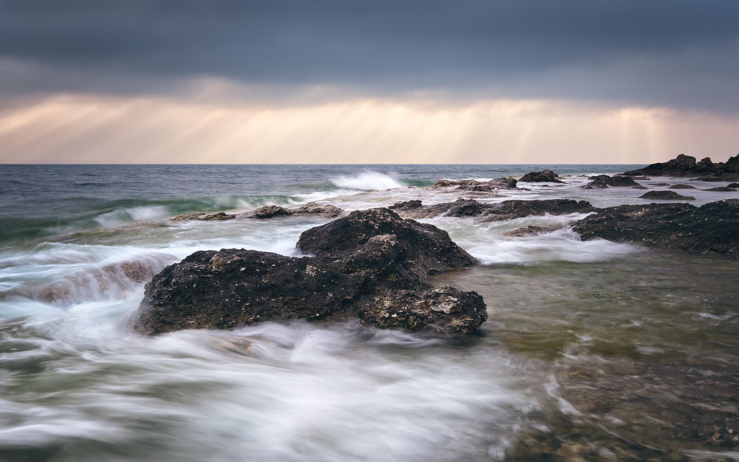 The mornig sea floats between the rocks