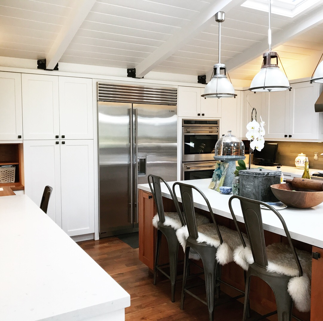 Organized kitchen with with cabinets, stainless steel appliances and industrial decor.